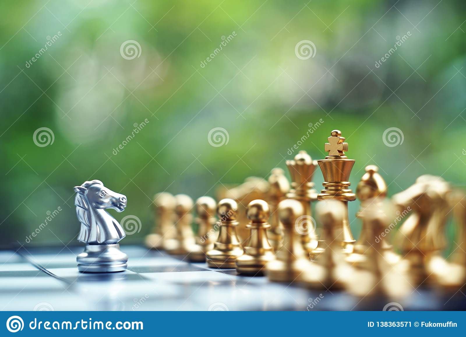 Chess board game. Fighting between silver and golden team. Business competitive and strategy planning concept.