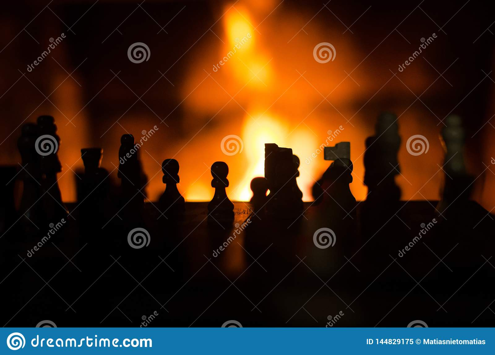 Chess figures silhouette with fire in the background