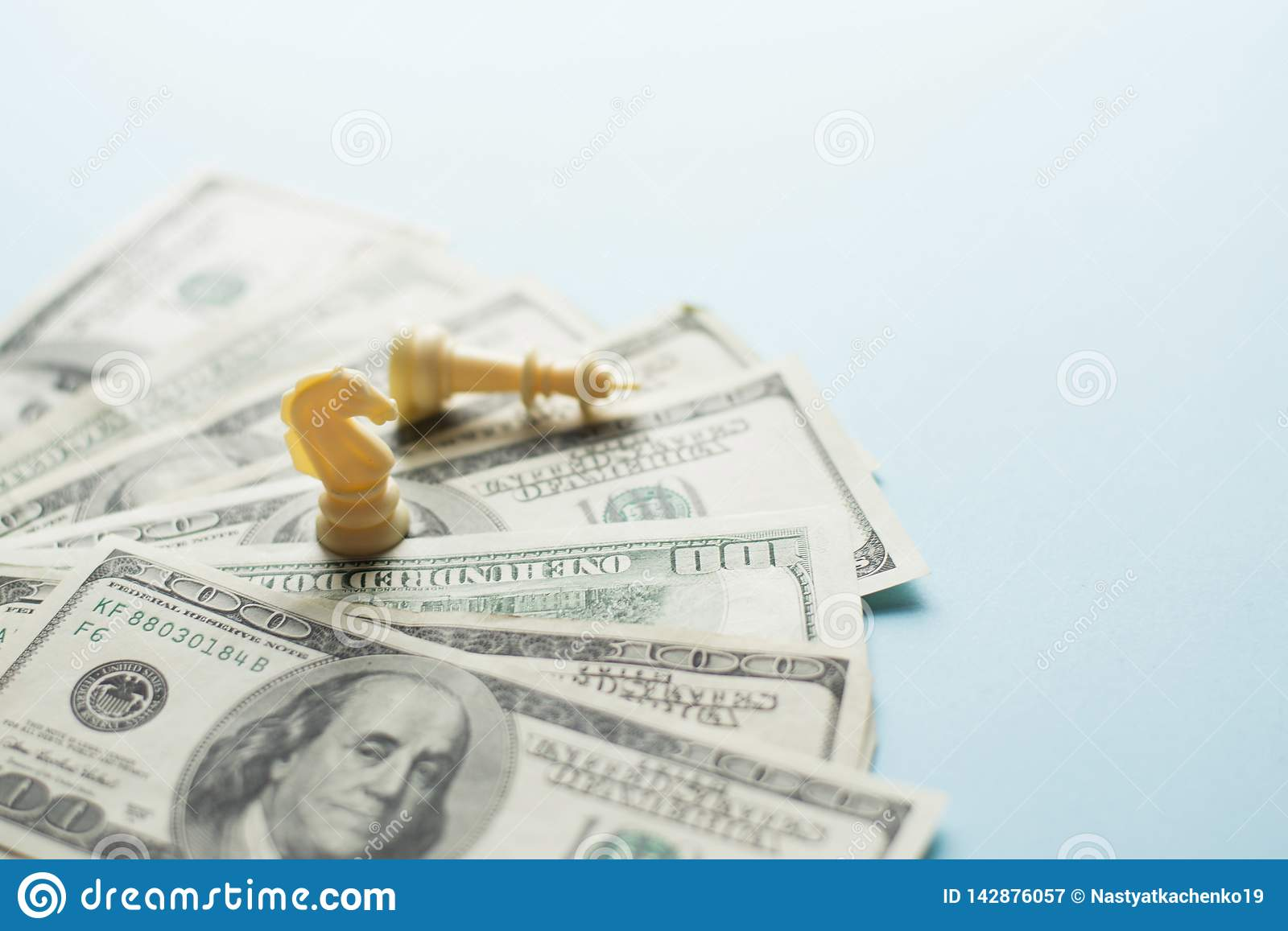 Chess game figures and US dollars on blue background with selective focus , business strategy planning. success