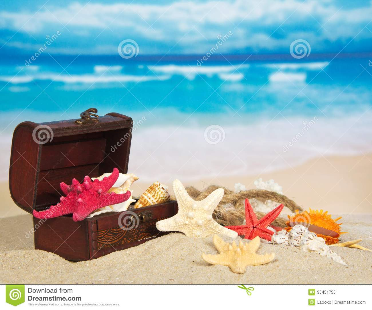 Chest with cockleshells and stars on sea sand