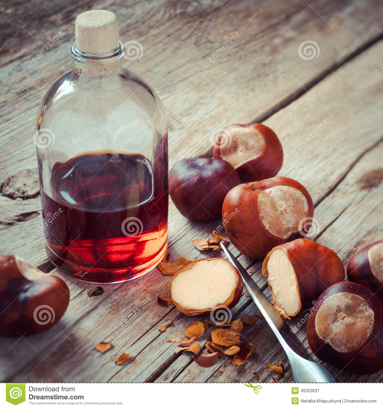 Chestnuts, knife and bottle with tincture on wooden table, herba