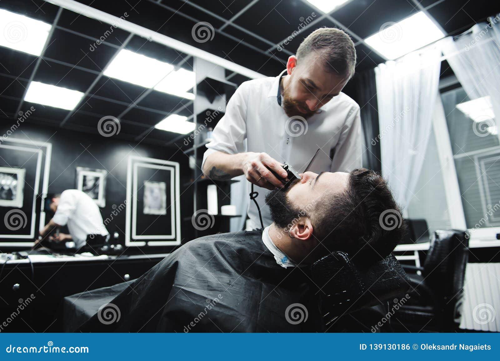Cheveux de coupes et barbe principaux des hommes dans le raseur-coiffeur, coiffeur