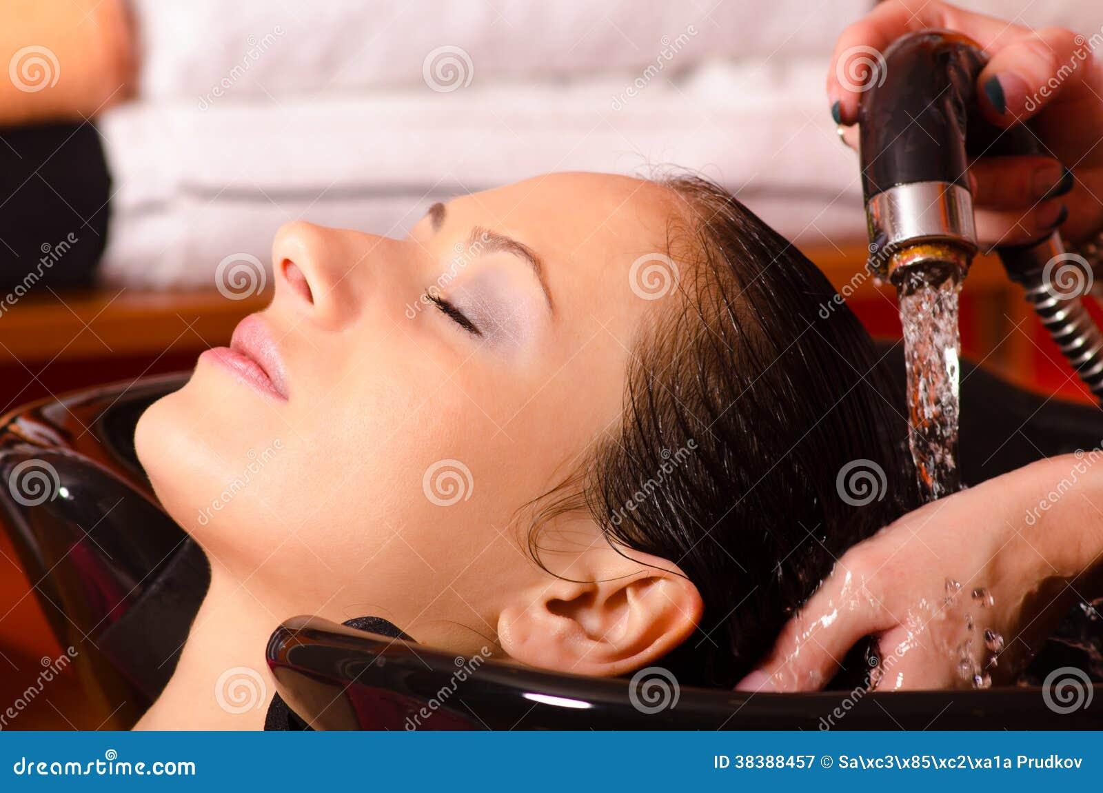 Cheveux de lavage de fille au coiffeur