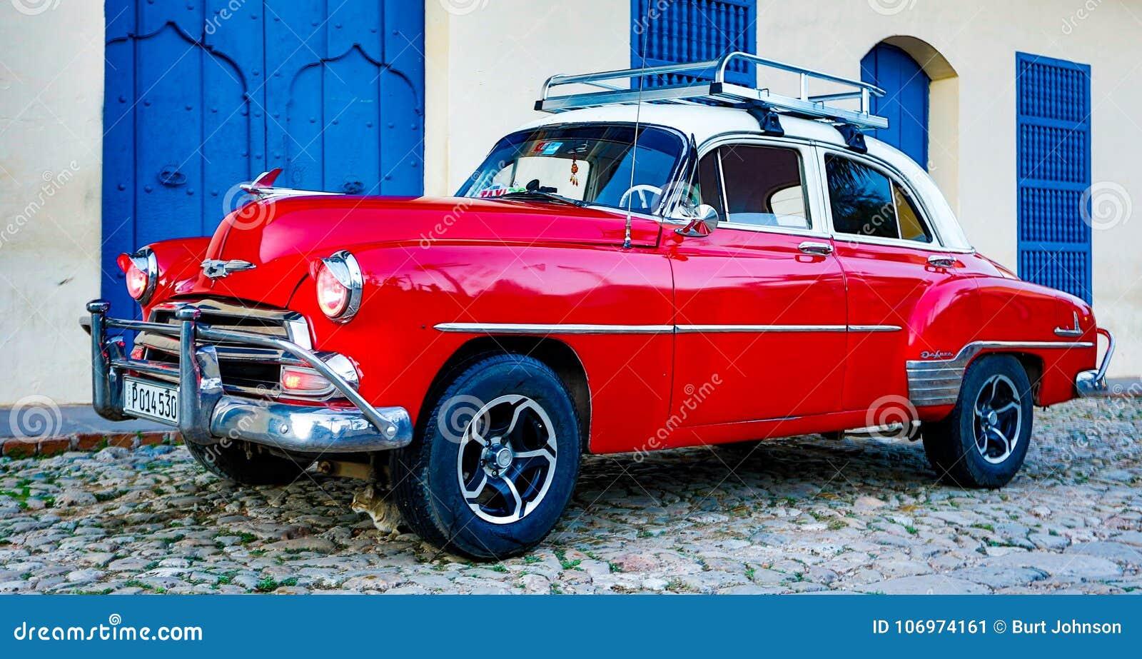Chevy clássico vermelho é estacionado na frente de uma casa