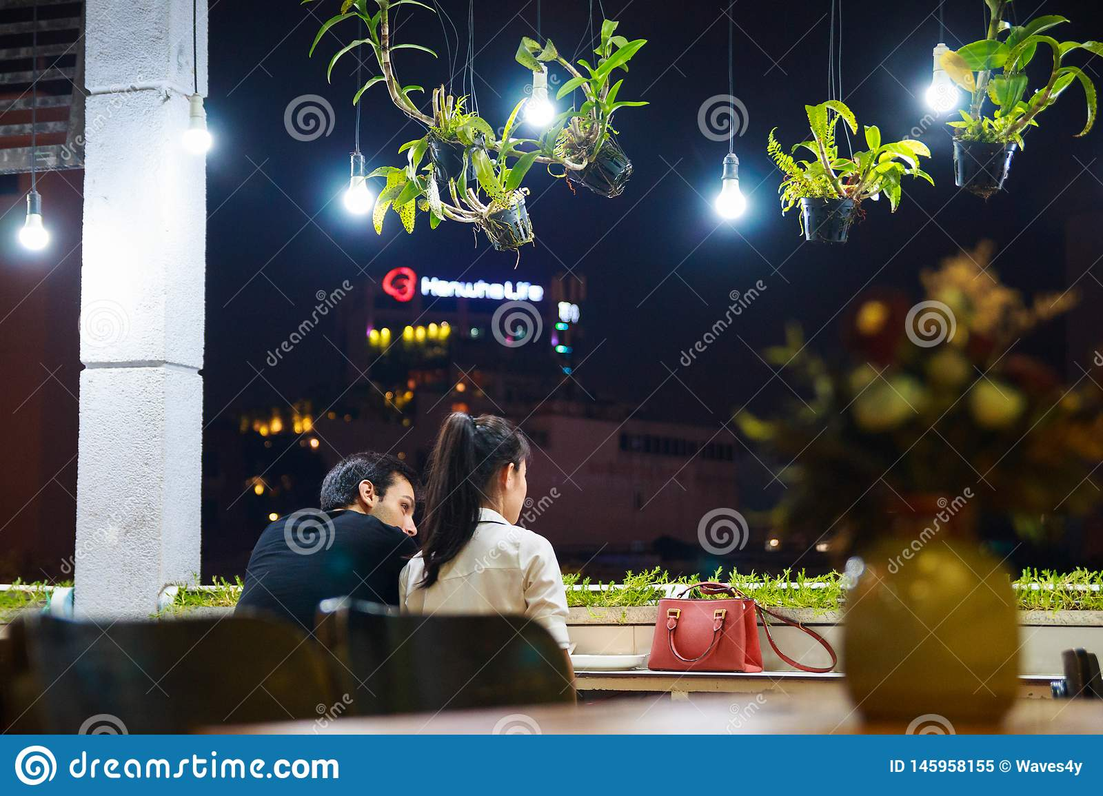 Ho Chi Minh city, Vietnam - December 2018: couple seats on the balcony of cozy cafe with lanterns and green plants.