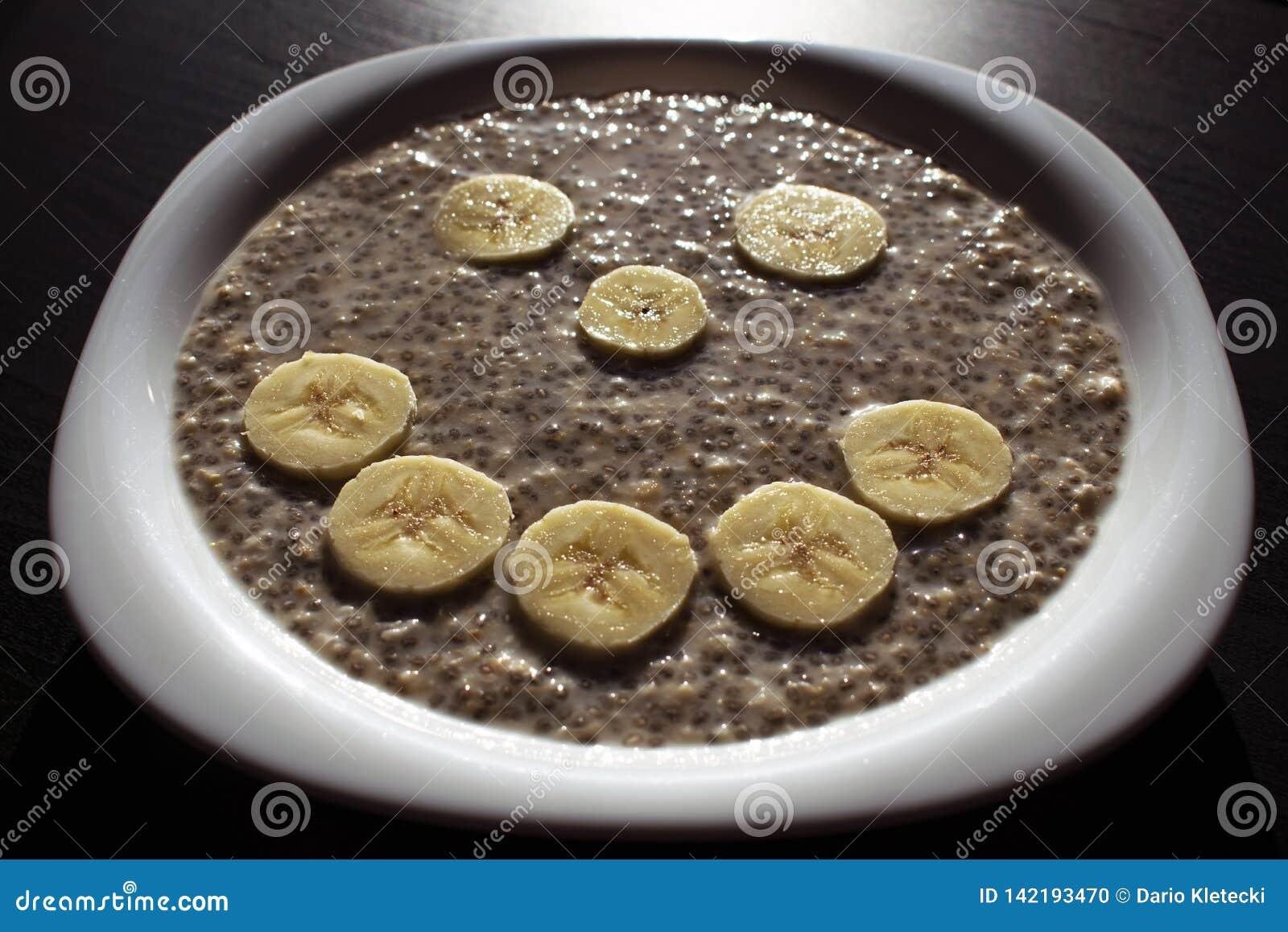 Chia种子和燕麦剥落在水中,当香蕉切片被安排在兴高采烈的面孔在一块白色板材