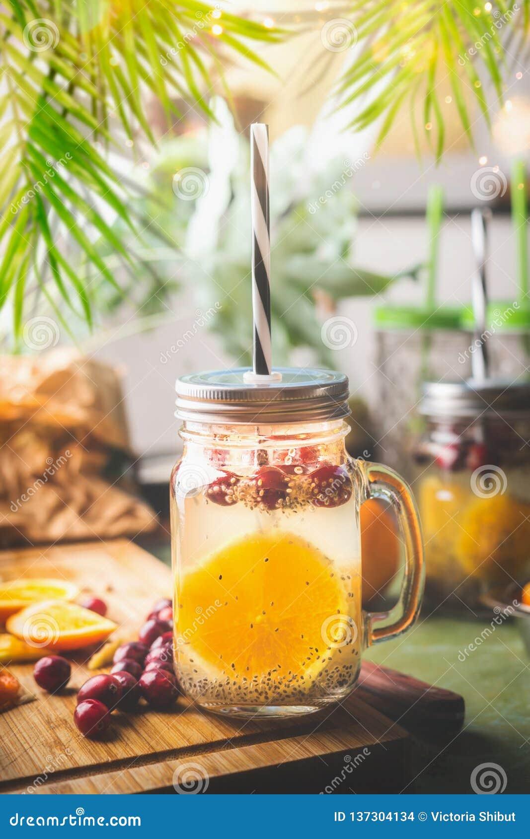 Chia种子与橙色果子切片、柠檬汁和蔓越桔的戒毒所水在有吸管的玻璃瓶子在厨房用桌上
