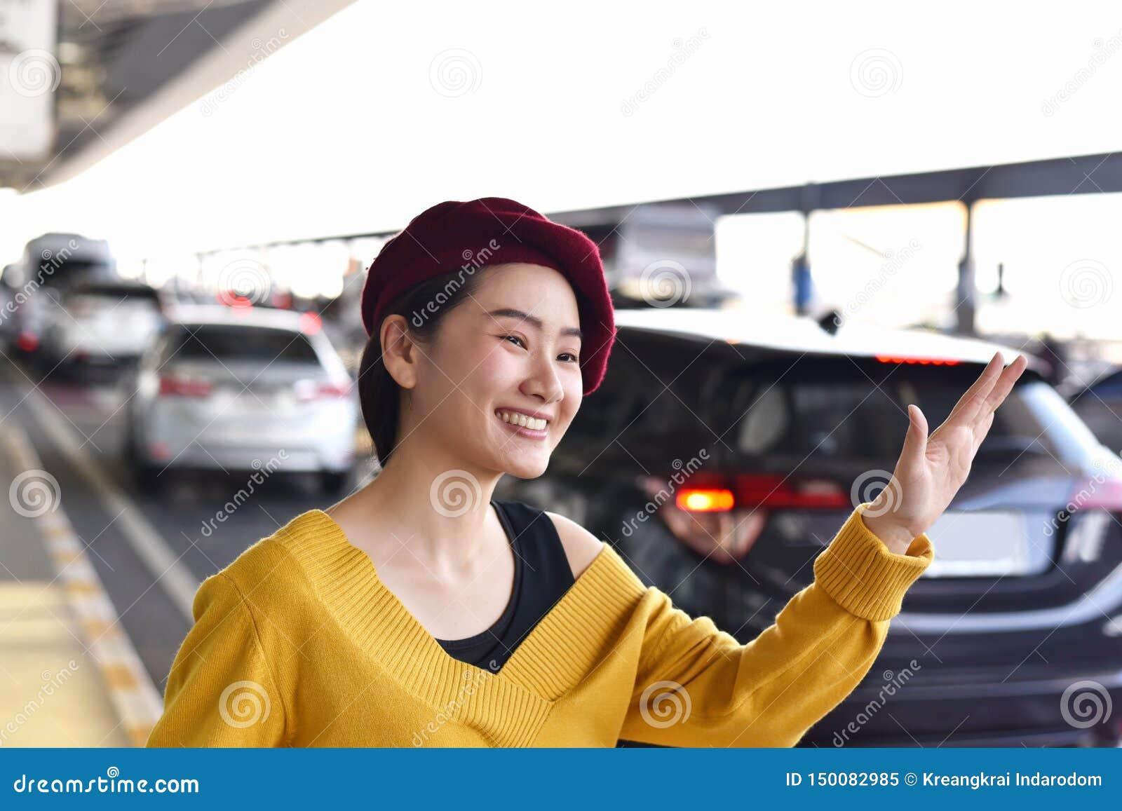 Chiamata asiatica della donna un servizio dell automobile del taxi all aeroporto