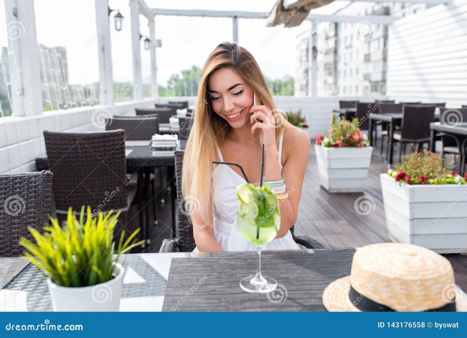 Chiamate allegre della ragazza sul telefono, caffè di estate, aria fresca sulla veranda Vetro di cocktail bianco del vestito dall