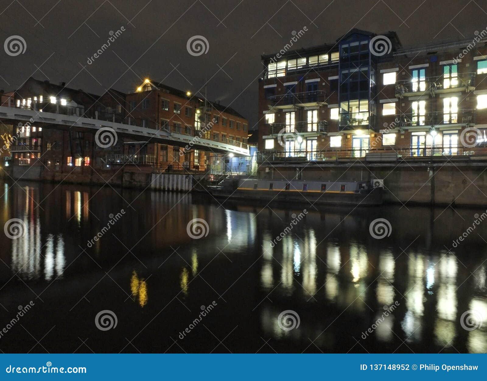 Chiamate che atterrano sul fiume Aire a Leeds alla notte con le luci di vecchie costruzioni storiche e gli appartamenti riflessi