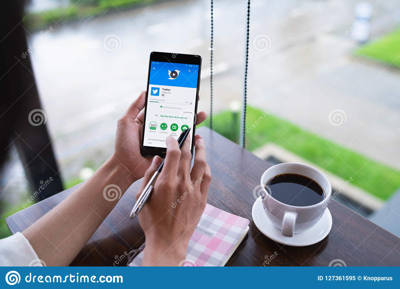 CHIANG MAI, THAILAND - August 18,2018: Woman hand holding HUAWEI with Twitter app on the screen.Twitter is an online news and soc