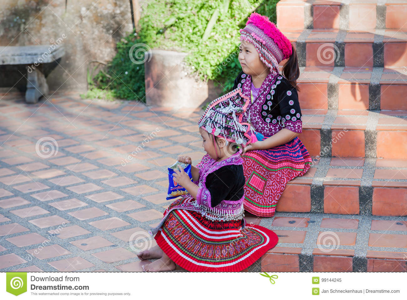Two Thai children in traditional clothes on the stairs to the Golden Temple of Chiang Mai.