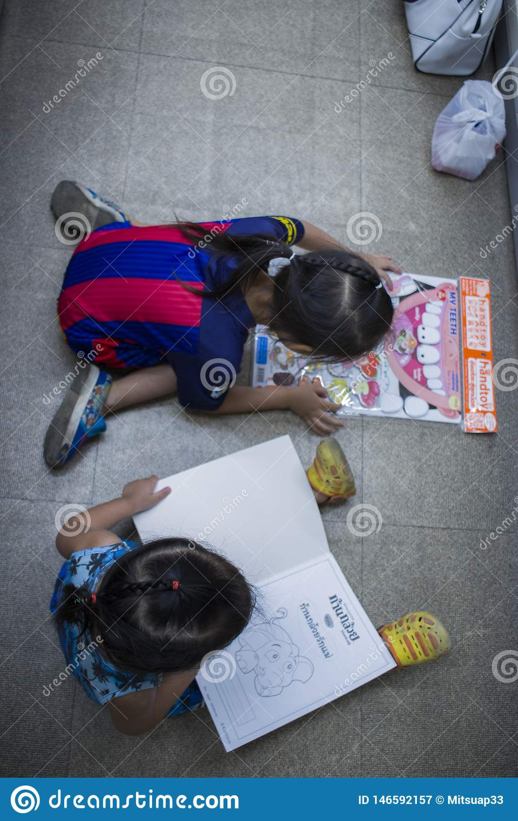 CHIANGMAI,THAILAND-MAY 3,2019 : two Little Child explores and reading a book   in book store top view