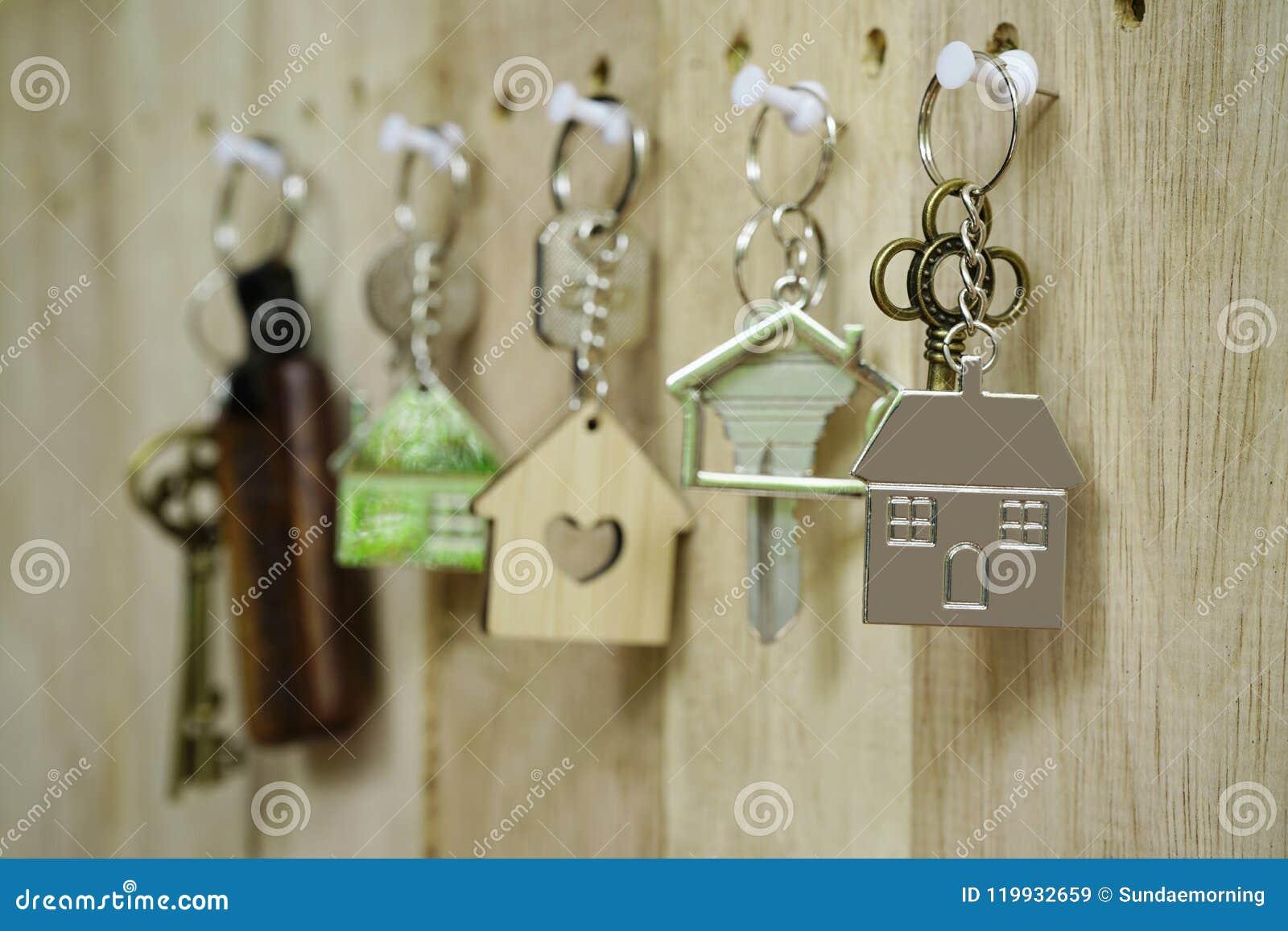 Chiave della Camera con l anello portachiavi domestico di legno che appende sul fondo di legno del bordo, concetto della propriet