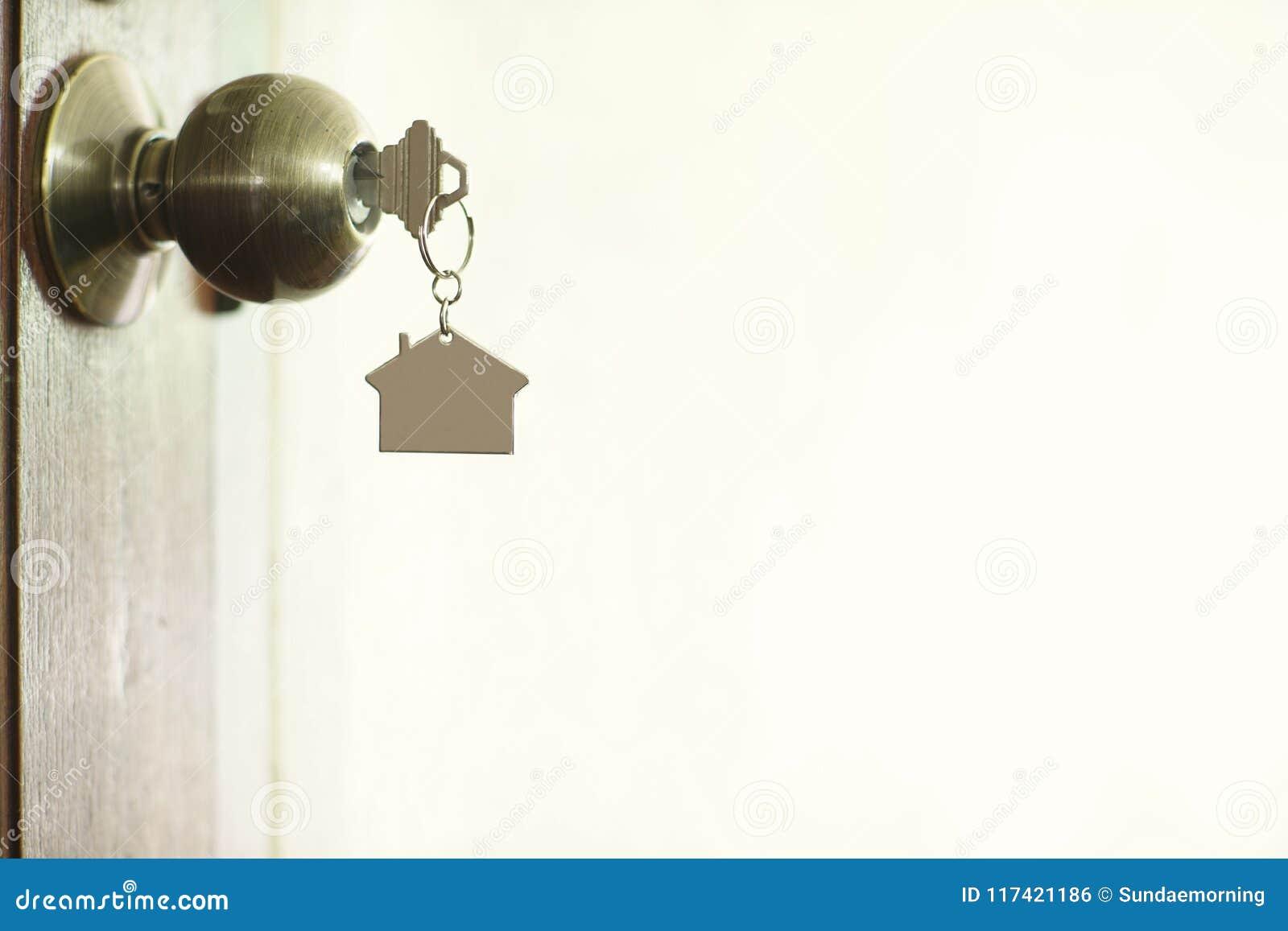 Chiave domestica con il keychain in buco della serratura, concetto della casa della proprietà