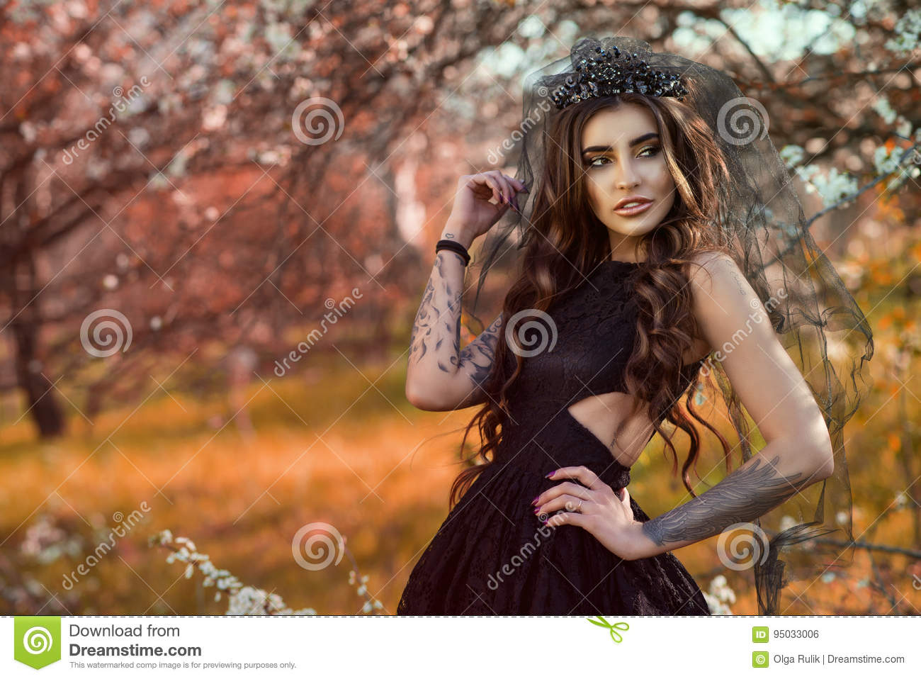 7bb6253e9f Chic dark-haired tattooed young woman wearing lace dress and black jewel  crown with veil
