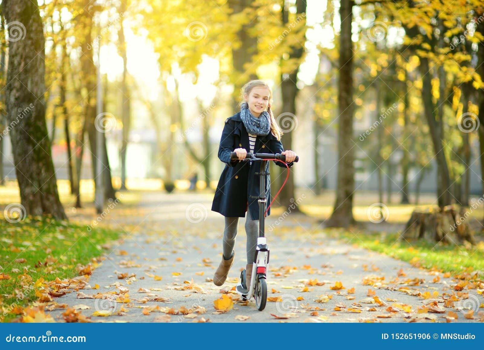 Chica joven adorable que monta su vespa en un parque de la ciudad en la tarde soleada del otoño Niño bonito del preadolescente qu
