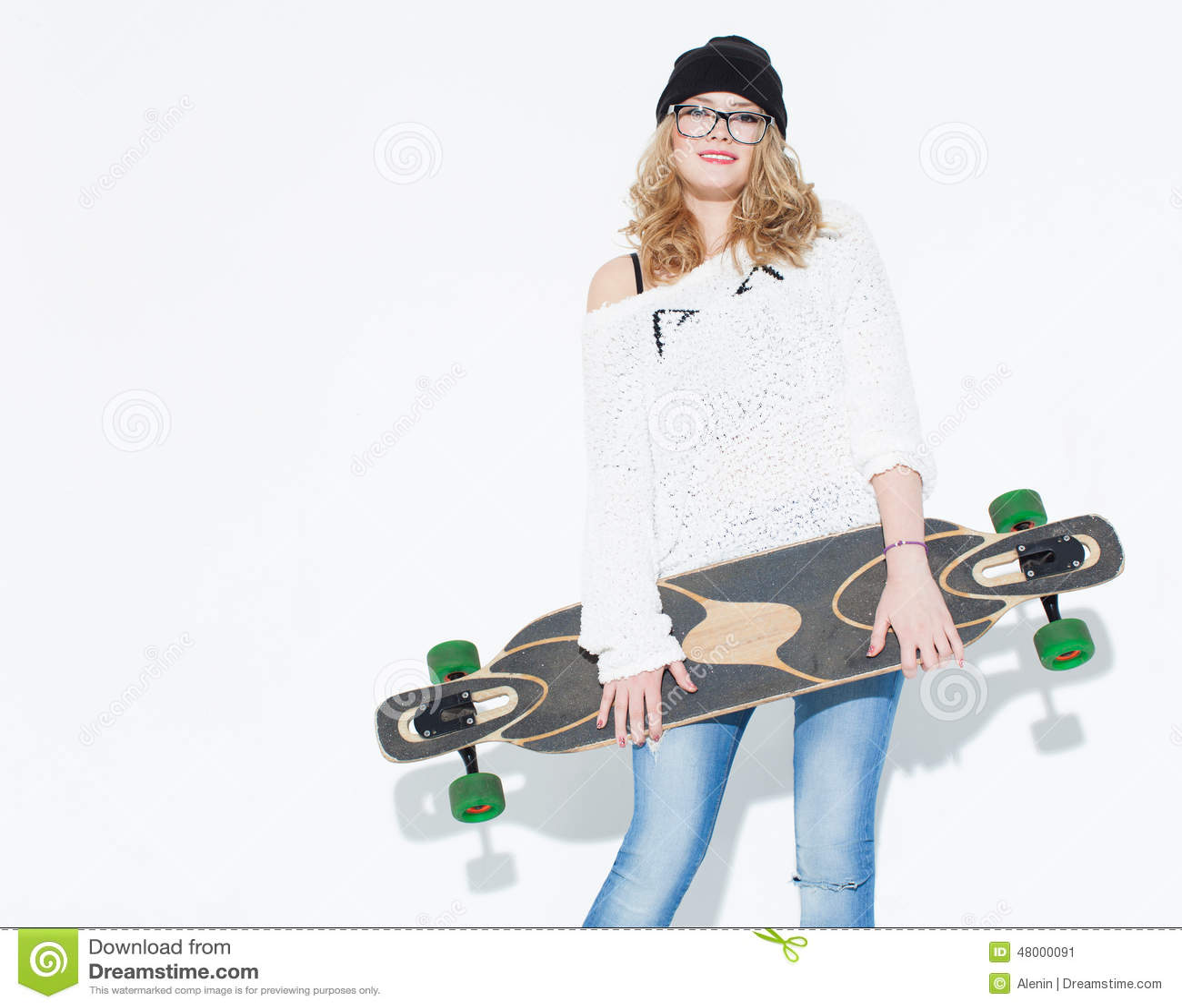 Chica joven alegre de moda de Bautiful en un suéter y un longboard blancos que presentan cerca de la pared blanca en el estudio