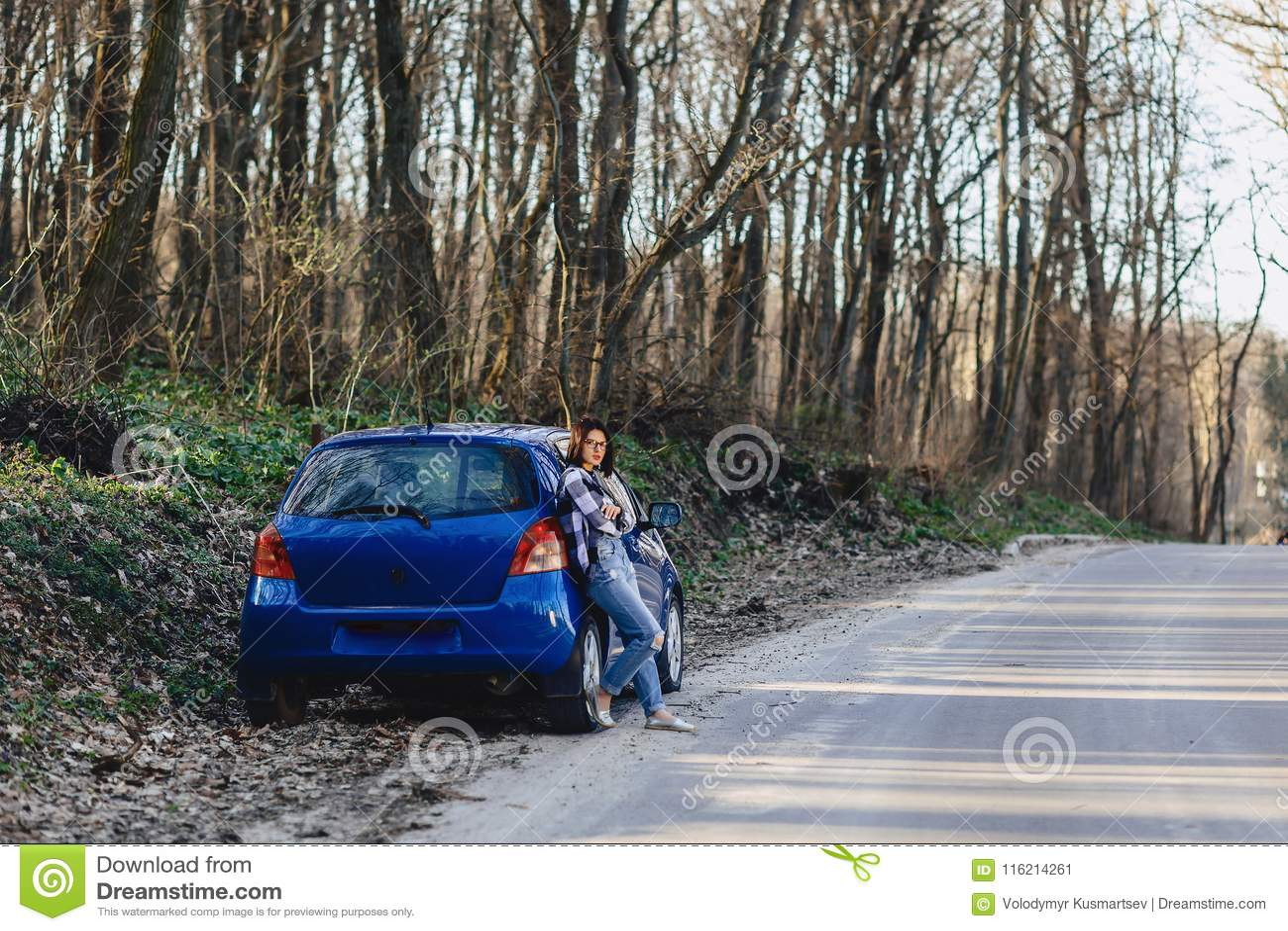 Chica joven atractiva en el camino cerca del coche