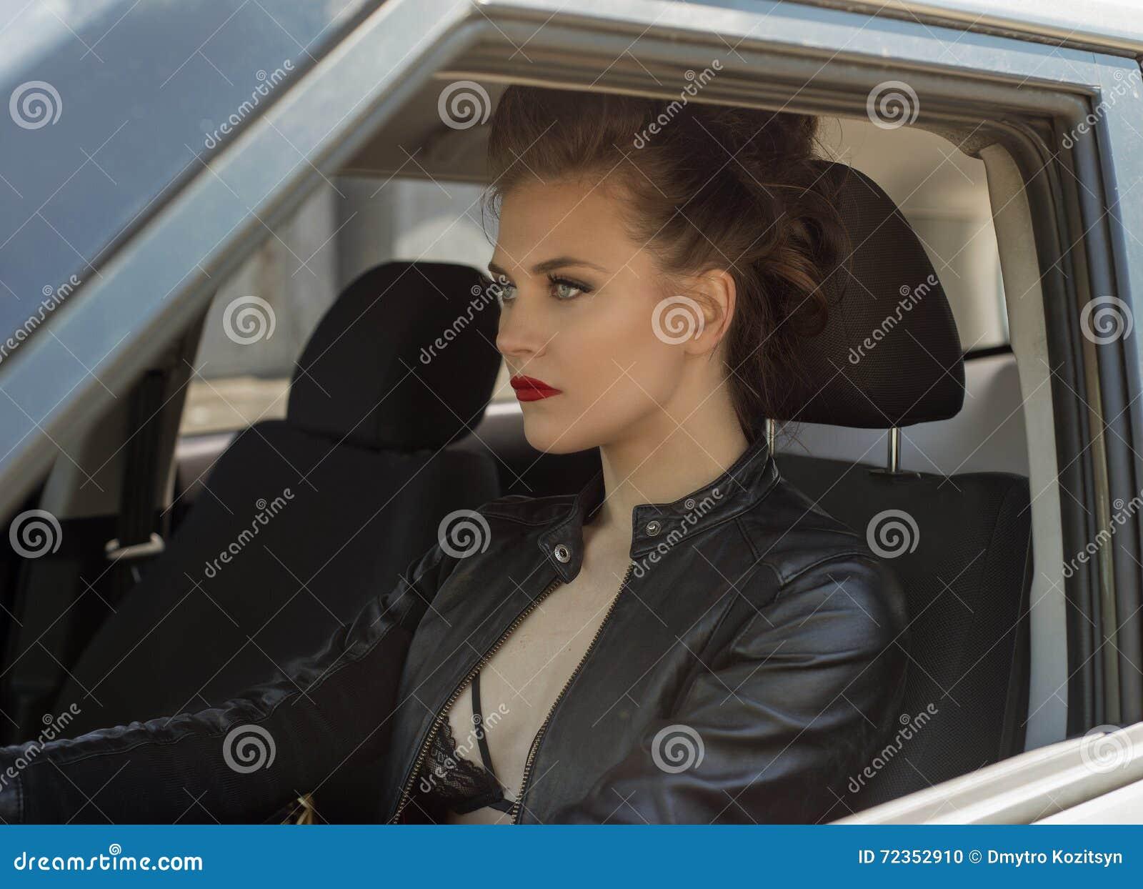 Chica joven atractiva que conduce el coche en la chaqueta de cuero