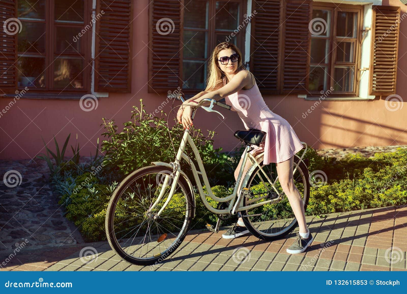 Chica joven atractiva sobre los vidrios que llevan y un vestido rosado po de una bicicleta