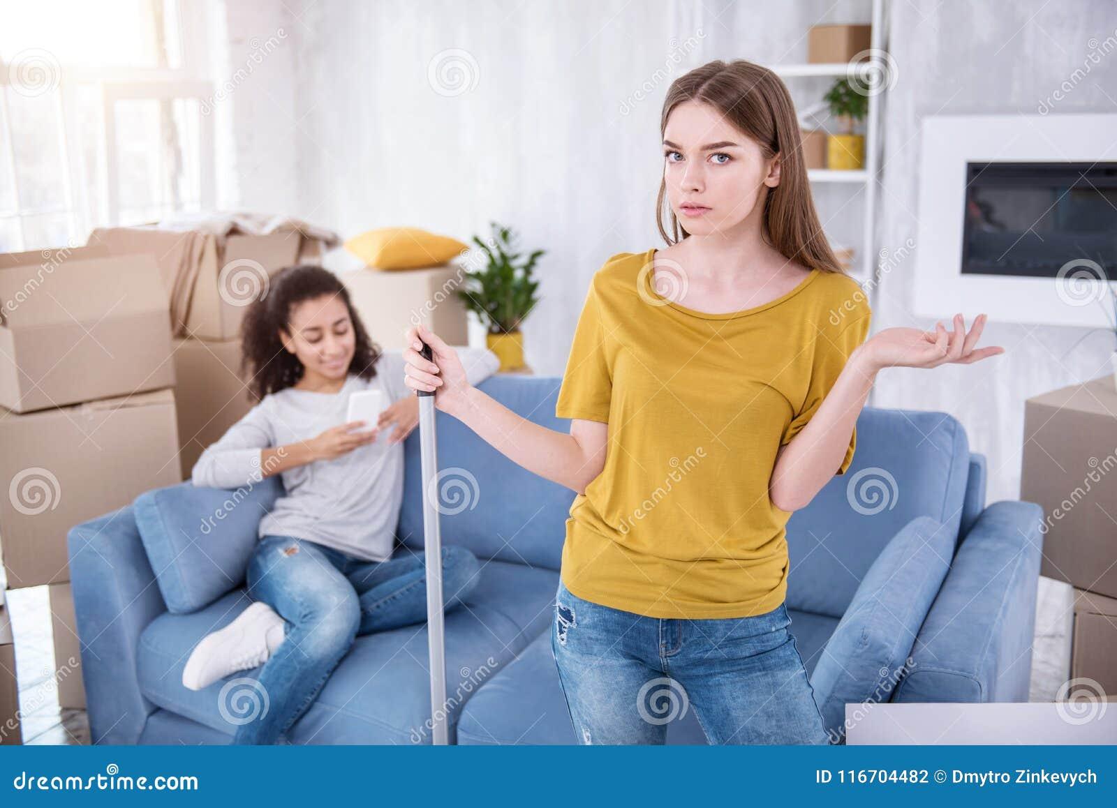 Chica joven bonita que está enojada en su compañero de cuarto perezoso