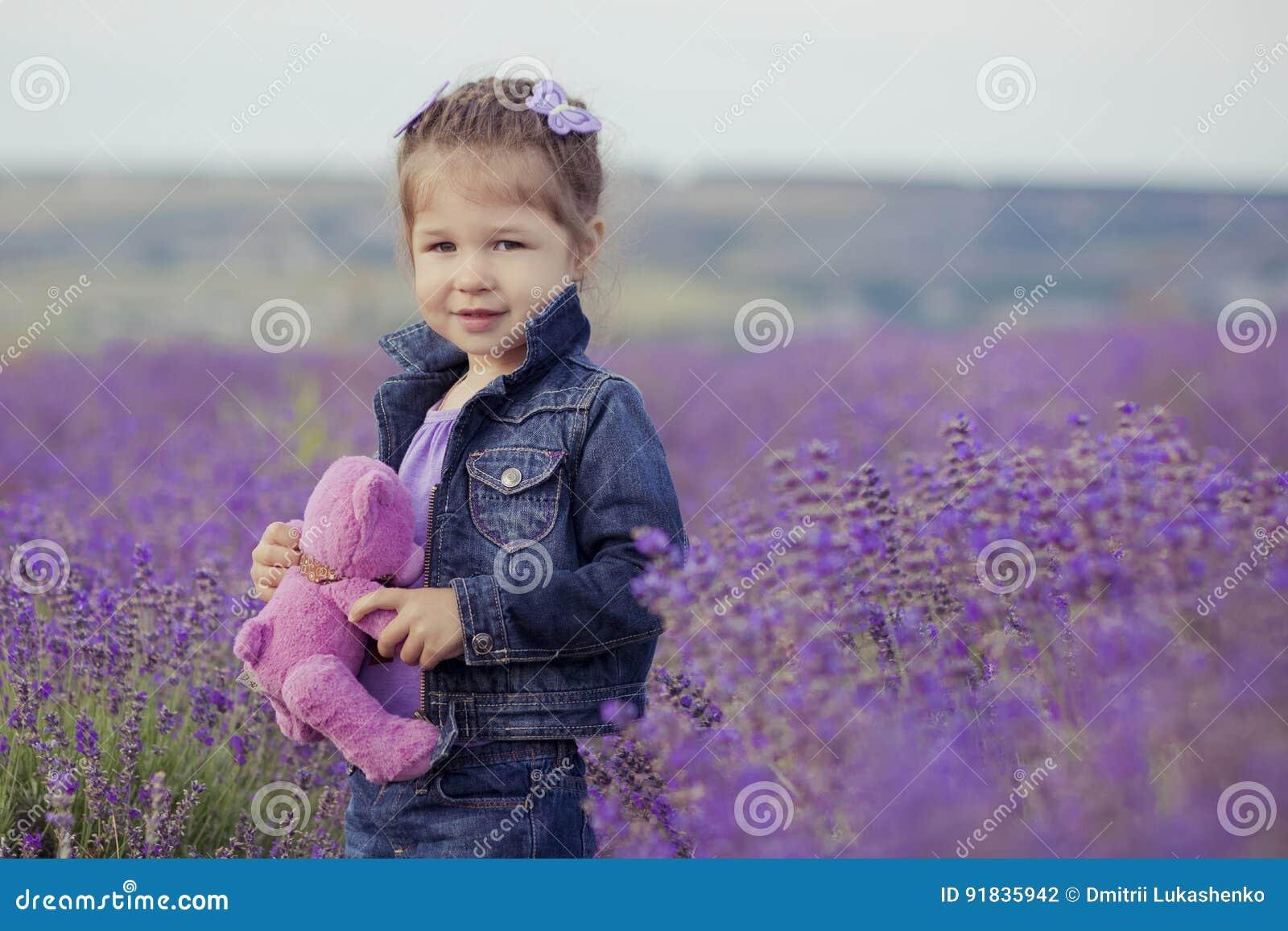 Chica joven bonita que se sienta en campo de la lavanda en navegante agradable del sombrero con la flor púrpura en ella