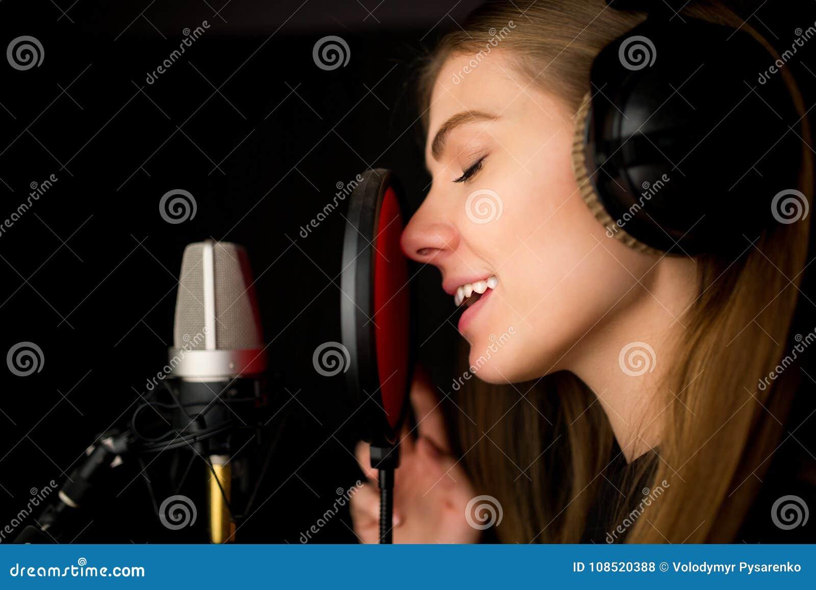 Chica joven cantante en el estudio de grabación