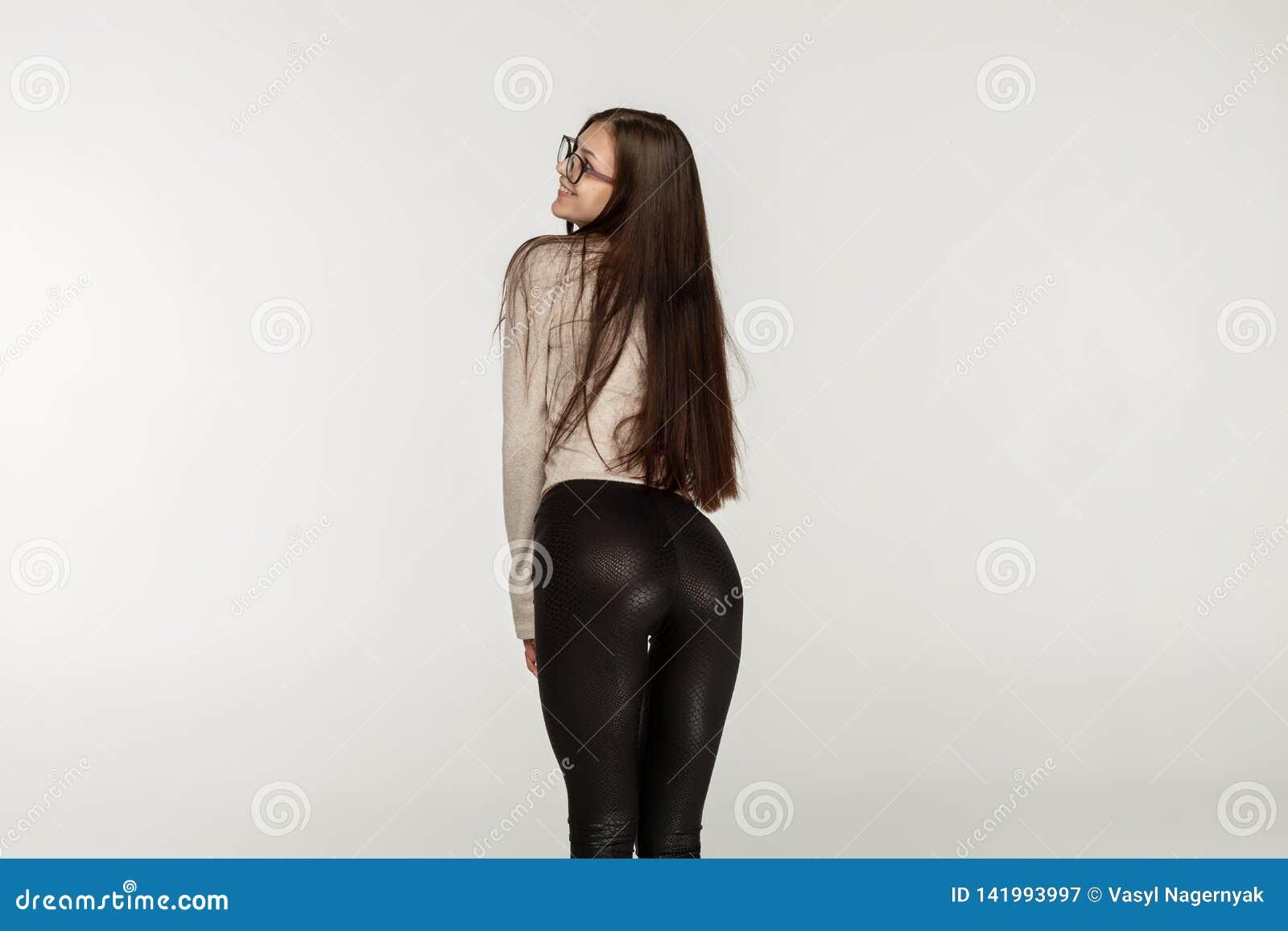 Chica joven con el pelo moreno en polainas negras