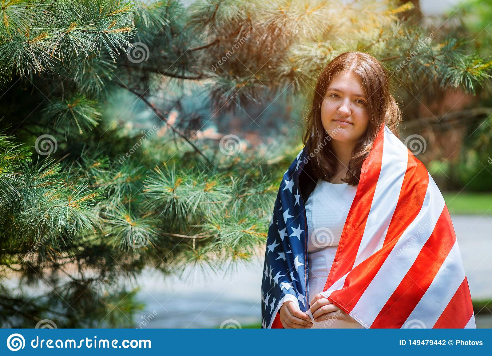 Chica joven con el vestido cl?sico que sostiene la bandera americana en el D?a de la Independencia del parque
