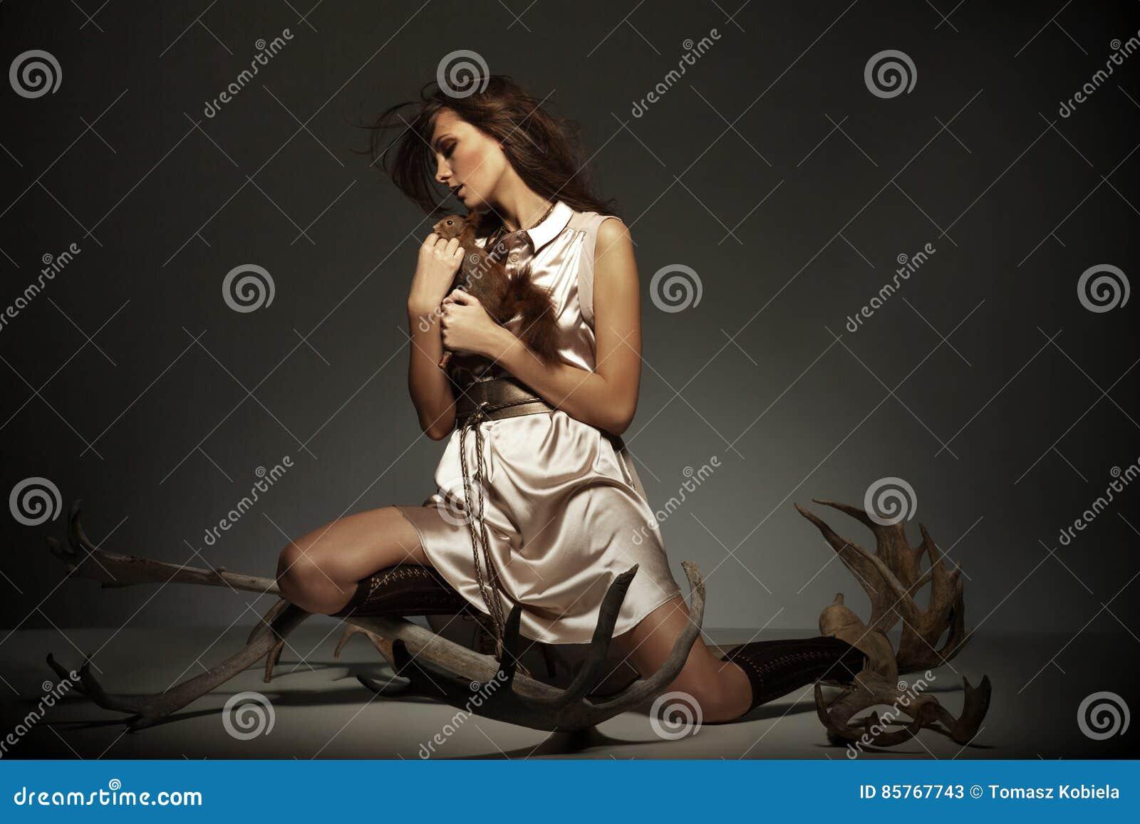 Chica joven con la ardilla que se sienta en estudio en vestido brillante encima