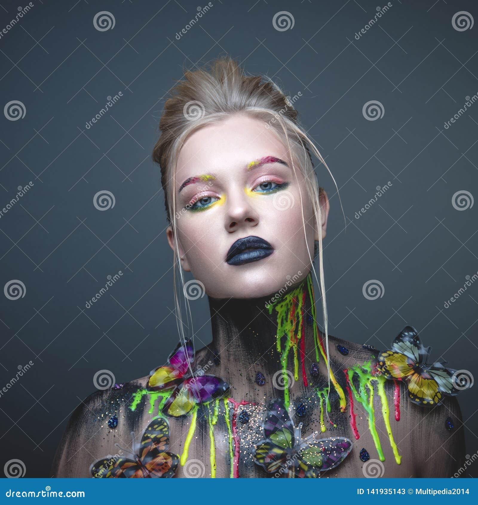 Chica joven con maquillaje creativo con las mariposas