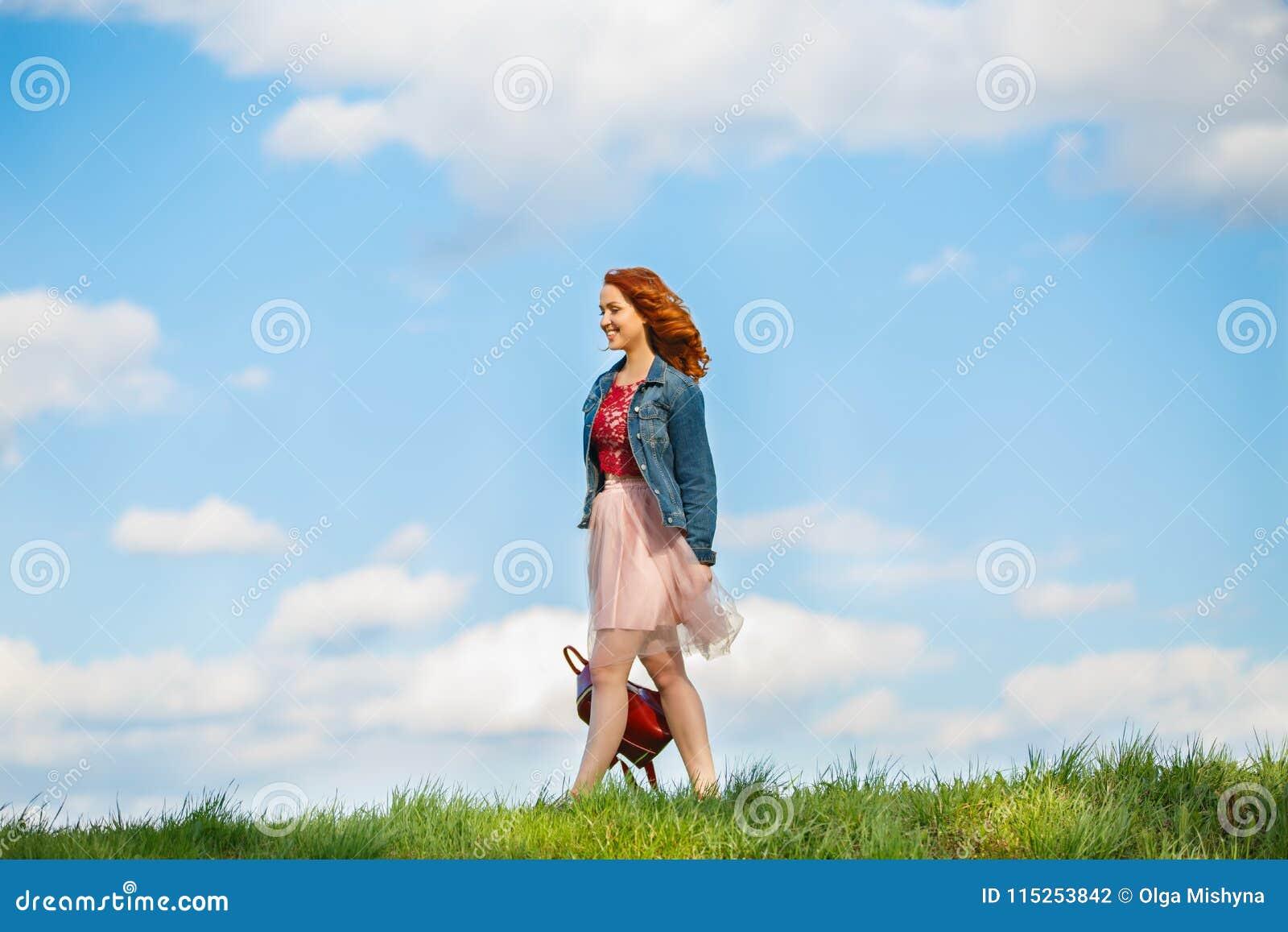 Chica joven con un bolso en fondo de la hierba verde y del cielo azul