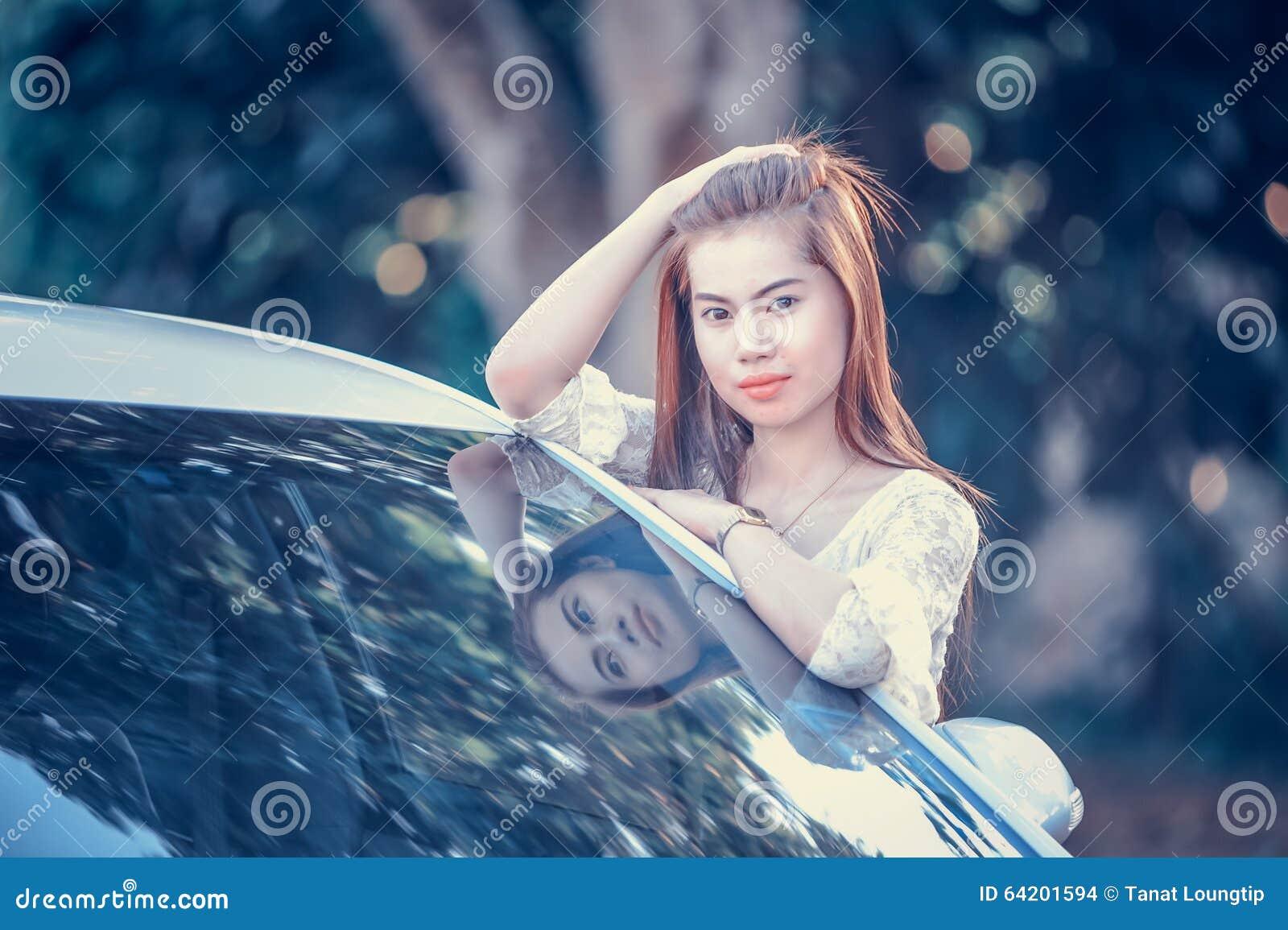 Chica joven de Asia en vestido con el coche de motor