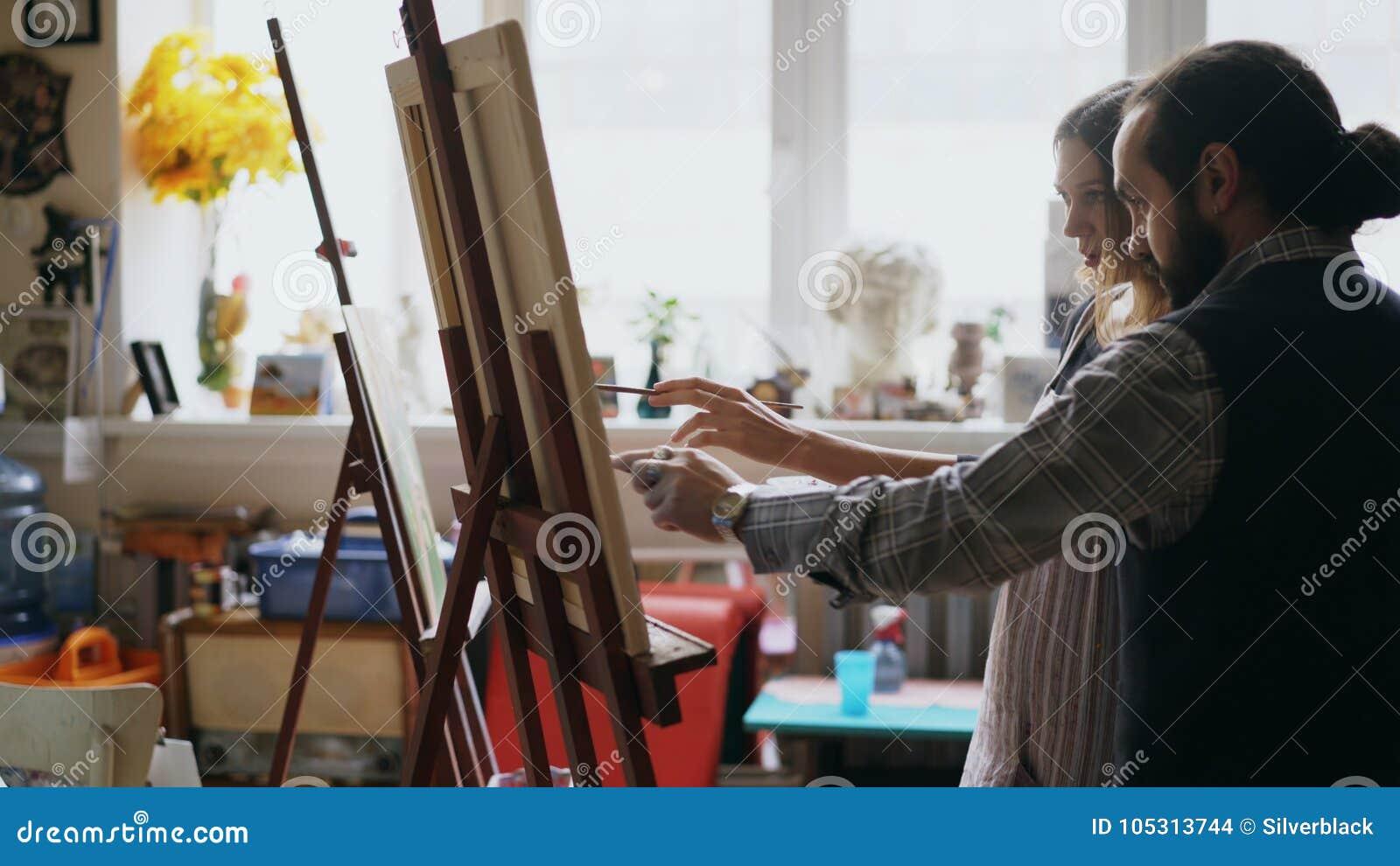 Chica joven de enseñanza del hombre experto del artista a las pinturas de dibujo y a explicar los fundamentos en estudio del arte
