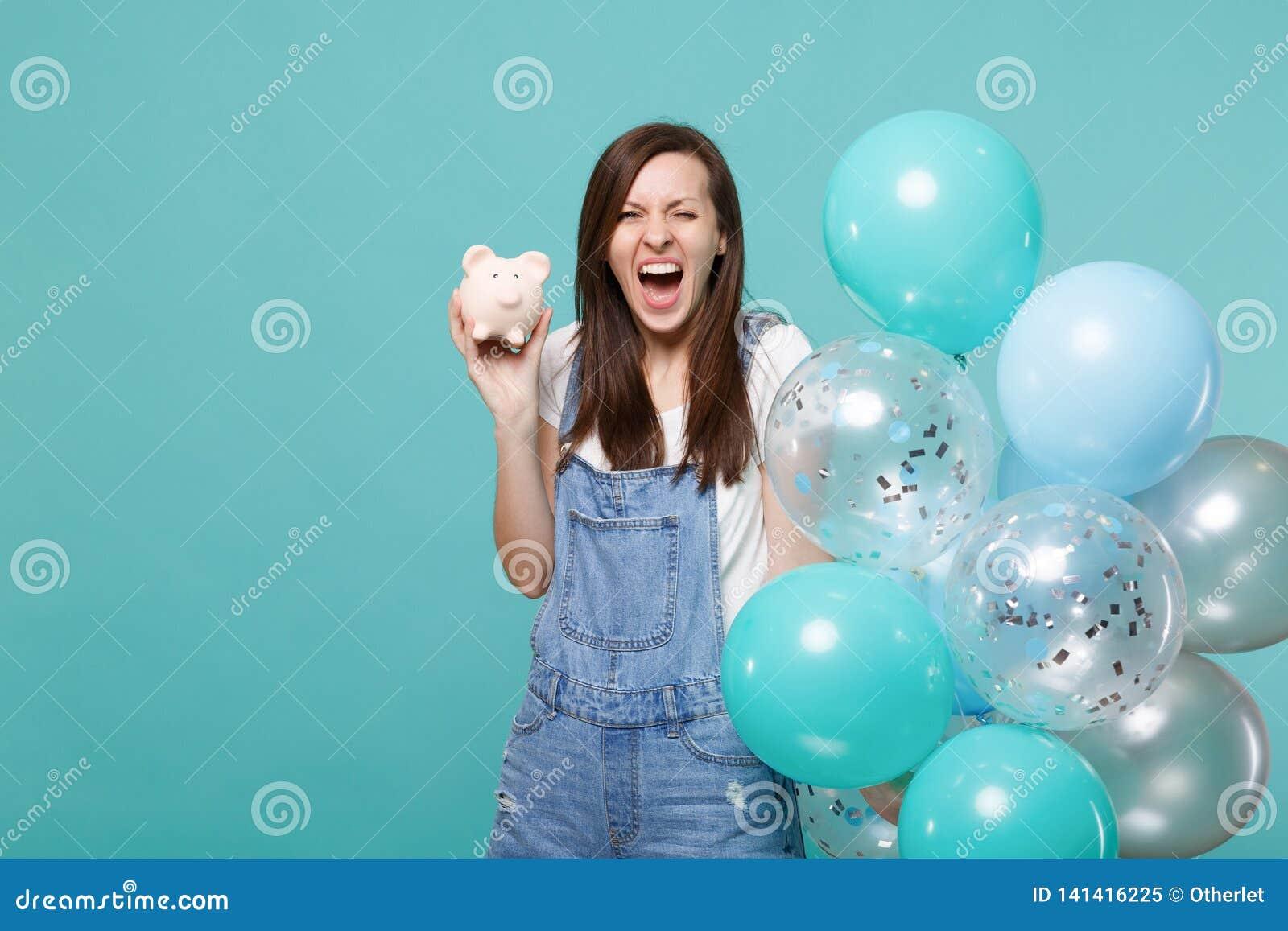 Chica joven divertida de griterío loca en la ropa del dril de algodón que sostiene el banco guarro del dinero que celebra con los