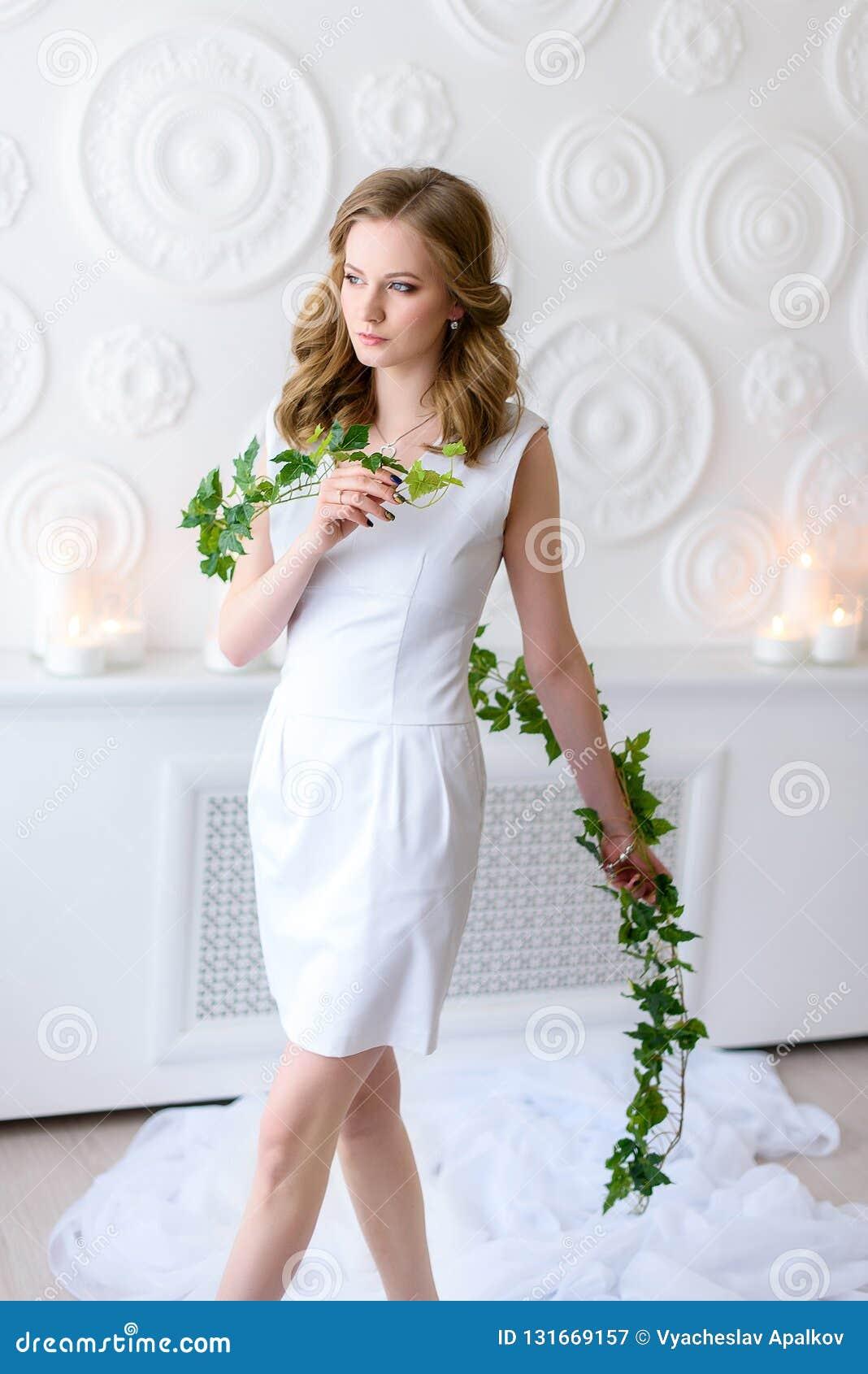 Chica joven en caminar blanco en un cuarto justo con una rama verde fresca larga en sus manos, vistazo serio a un lado