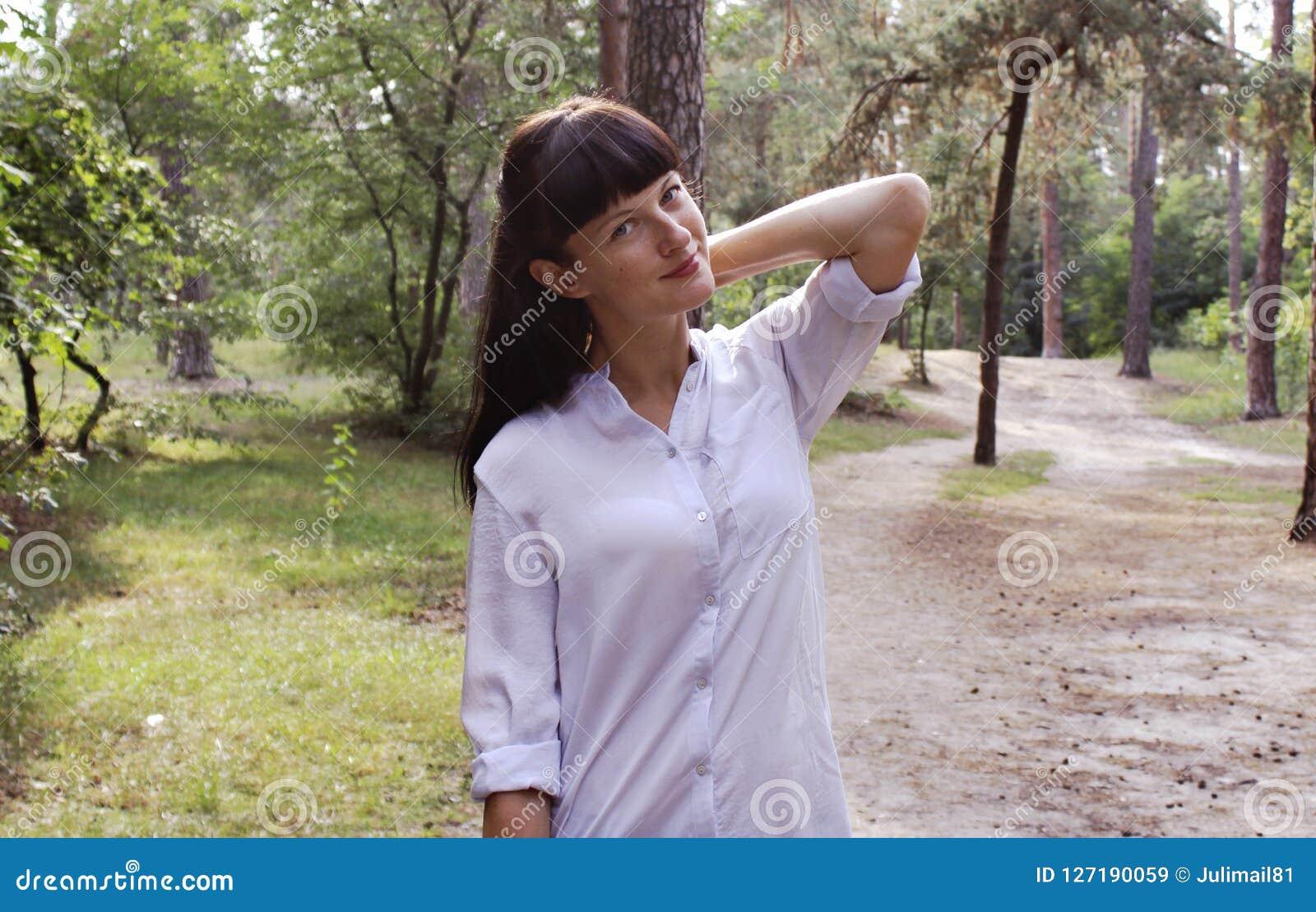 Chica joven en el parque que se coloca en el fondo del bosque