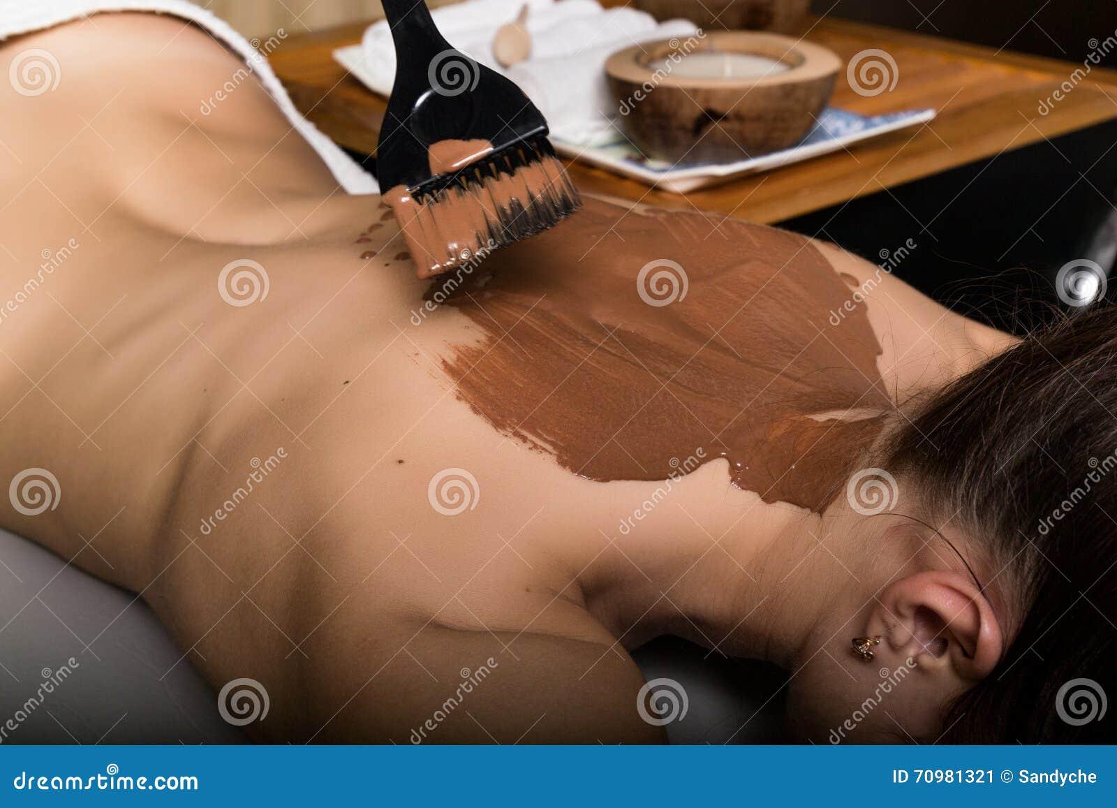Chica joven en el salón del balneario, tratamiento del abrigo del cuerpo del chocolate, rejuvenecimiento de la piel Concepto del