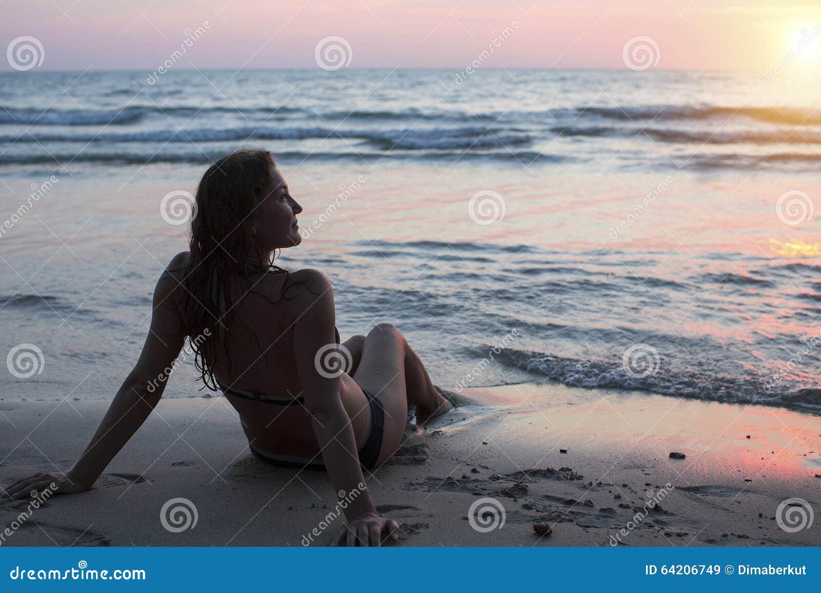 Chica joven en la playa del mar durante puesta del sol asombrosa Relájese