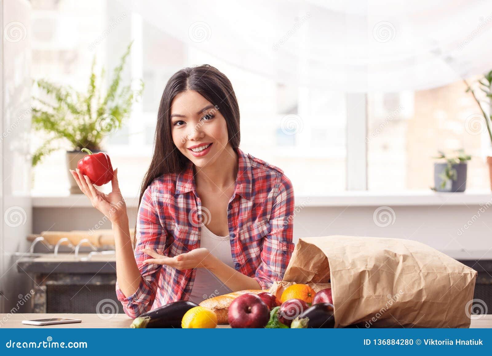 Chica joven en la situación sana de la forma de vida de la cocina que se inclina en el paprika de la demostración de la tabla a l