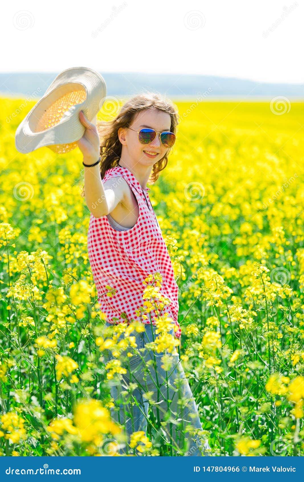 Chica joven en vestido a cuadros rojo y sunhat que presenta en campo de la violaci?n de semilla oleaginosa