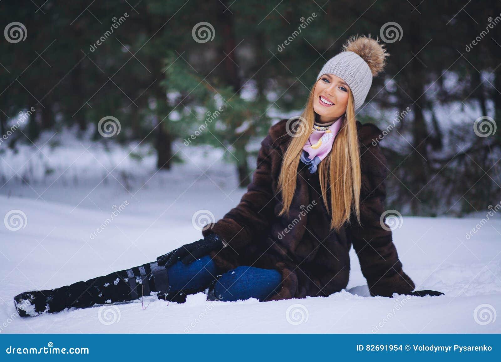 Chica joven feliz en el bosque del invierno