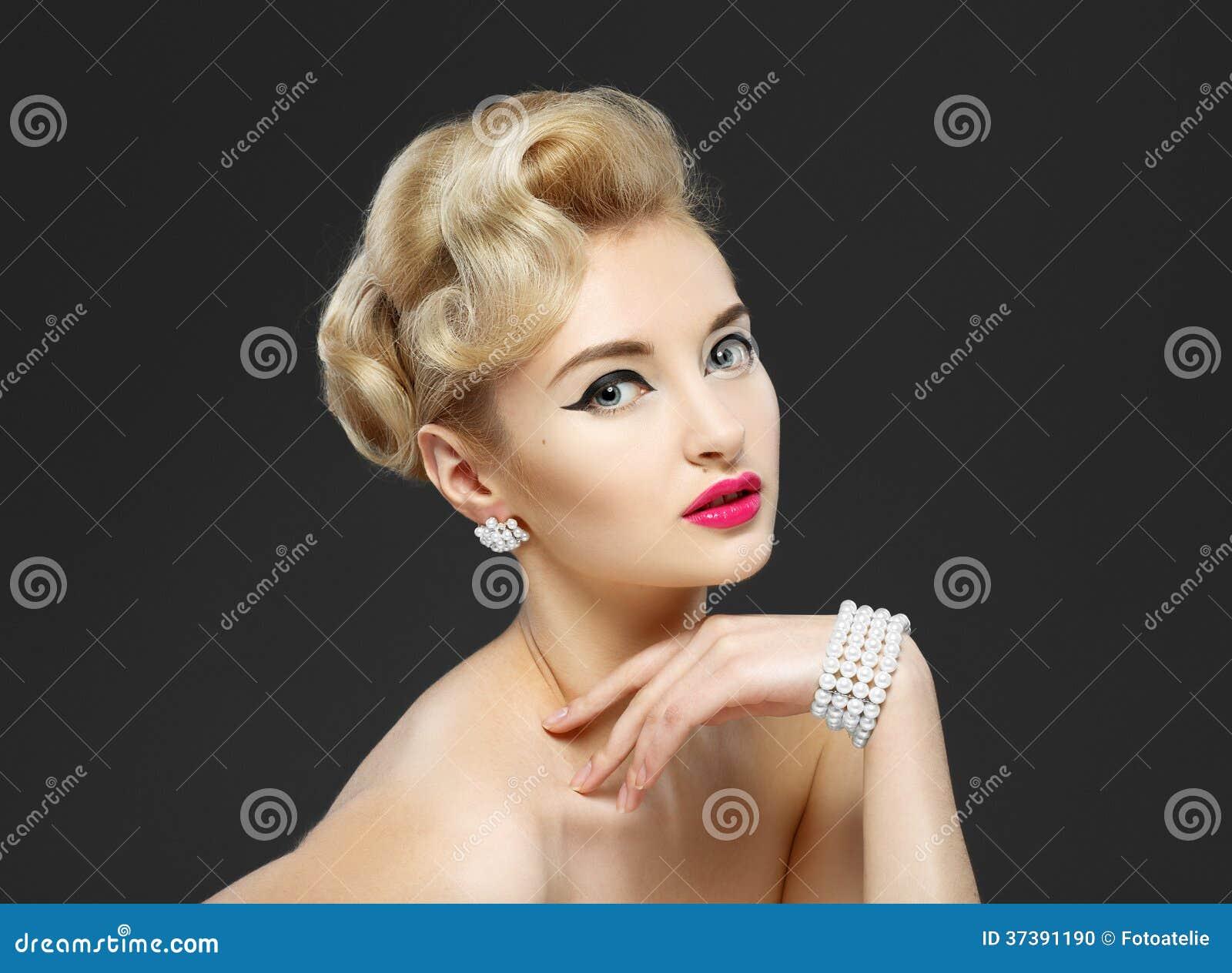9f4689b06 Chica joven hermosa con las joyas. Maquillaje en flecha del estilo de los  años 60. Fondo gris. Peinado.