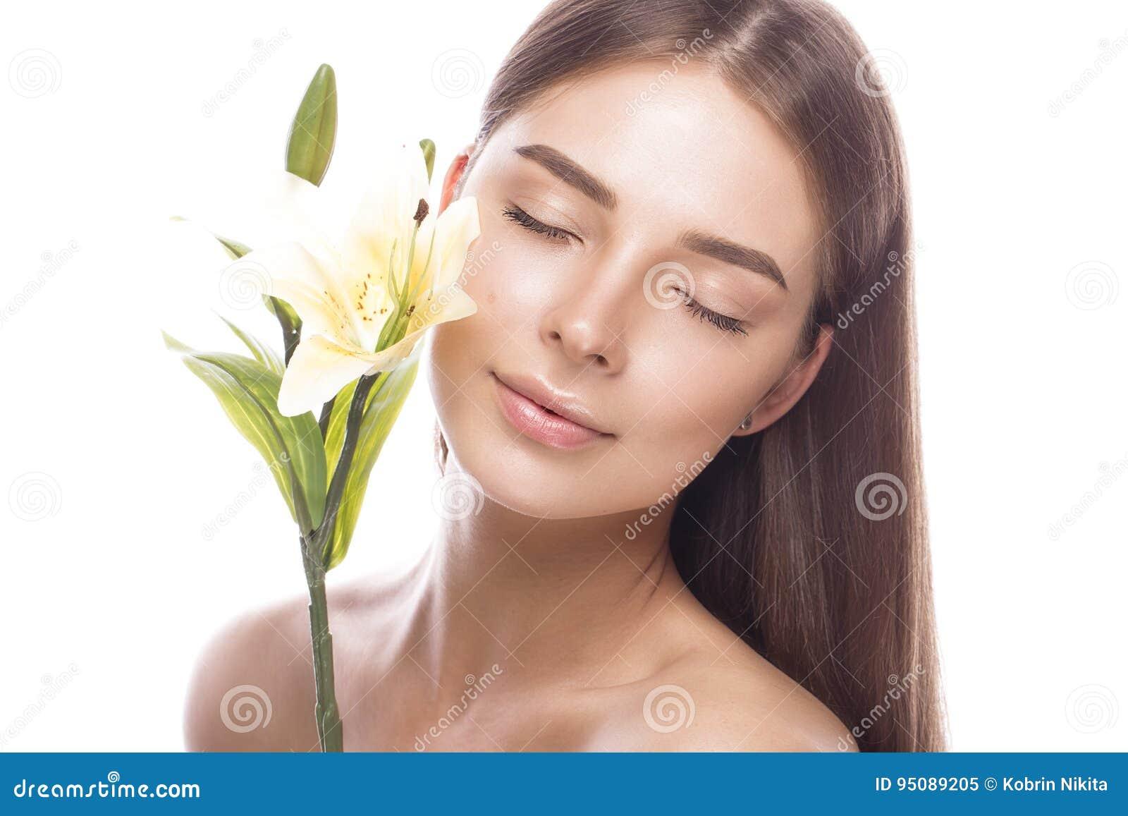Chica joven hermosa con un maquillaje natural ligero y piel perfecta con las flores en su mano Cara de la belleza