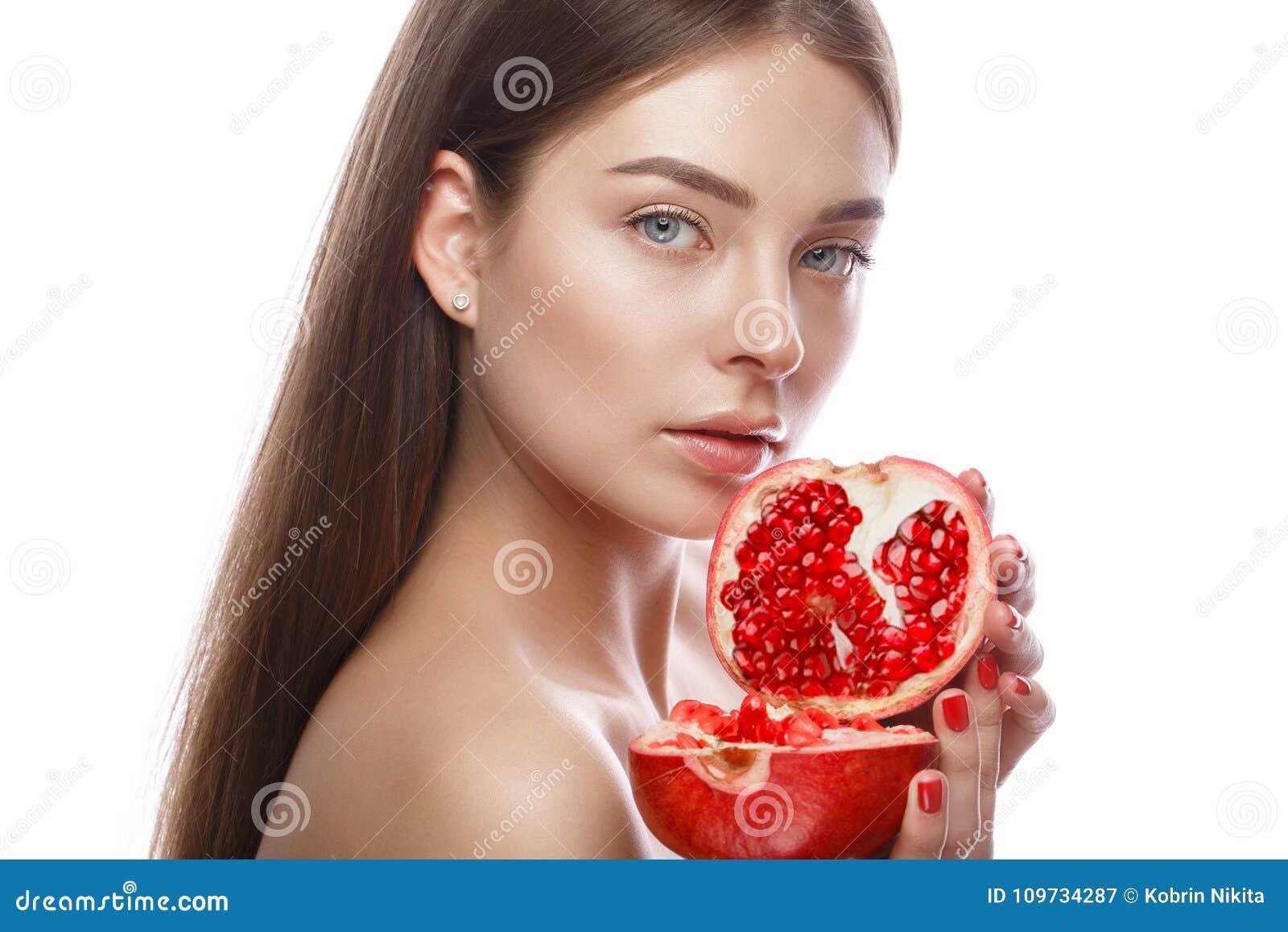 Chica joven hermosa con un maquillaje natural ligero y piel perfecta con la granada en su mano Cara de la belleza