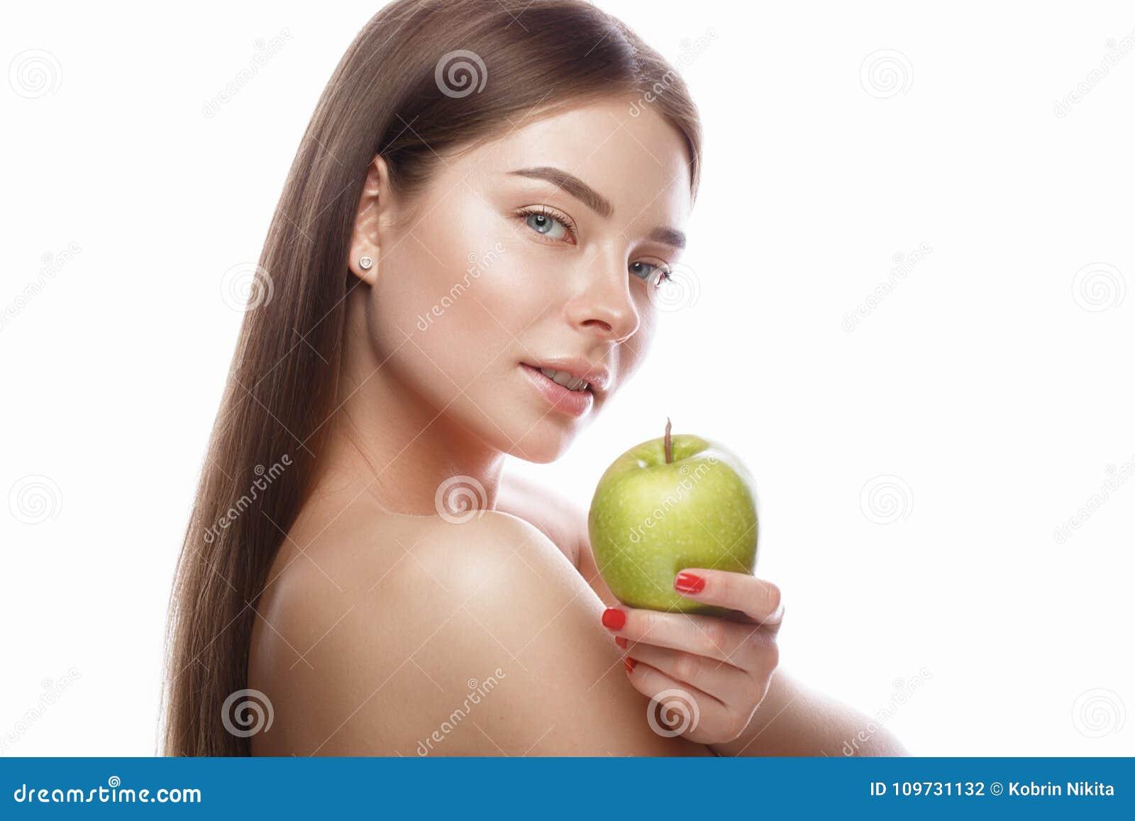 Chica joven hermosa con un maquillaje natural ligero y piel perfecta con la manzana en su mano Cara de la belleza