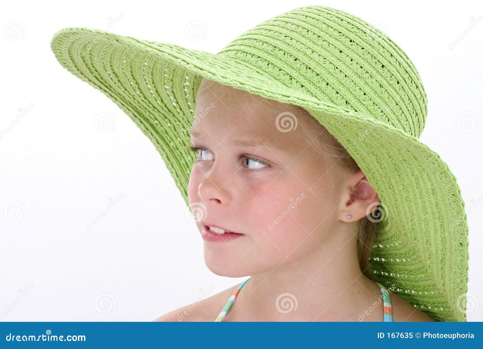 Chica joven hermosa en sombrero verde grande de la playa