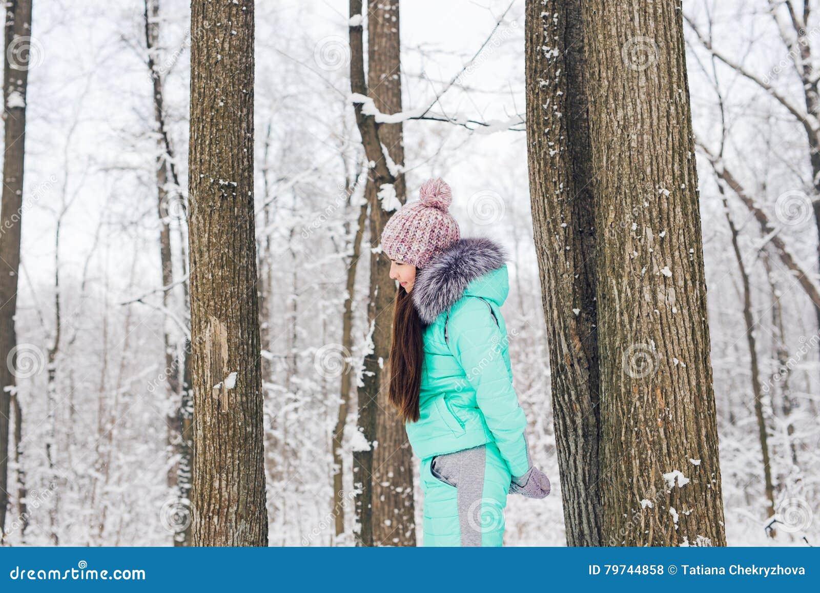 Chica joven hermosa en un bosque blanco del invierno