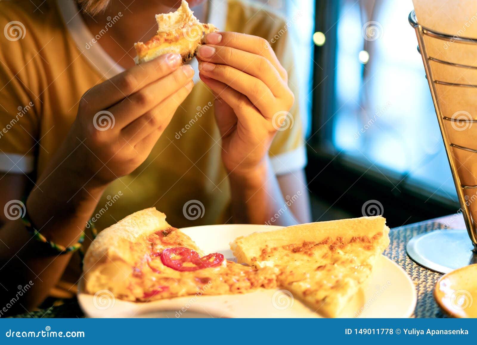 Chica joven hermosa que come una rebanada de pizza